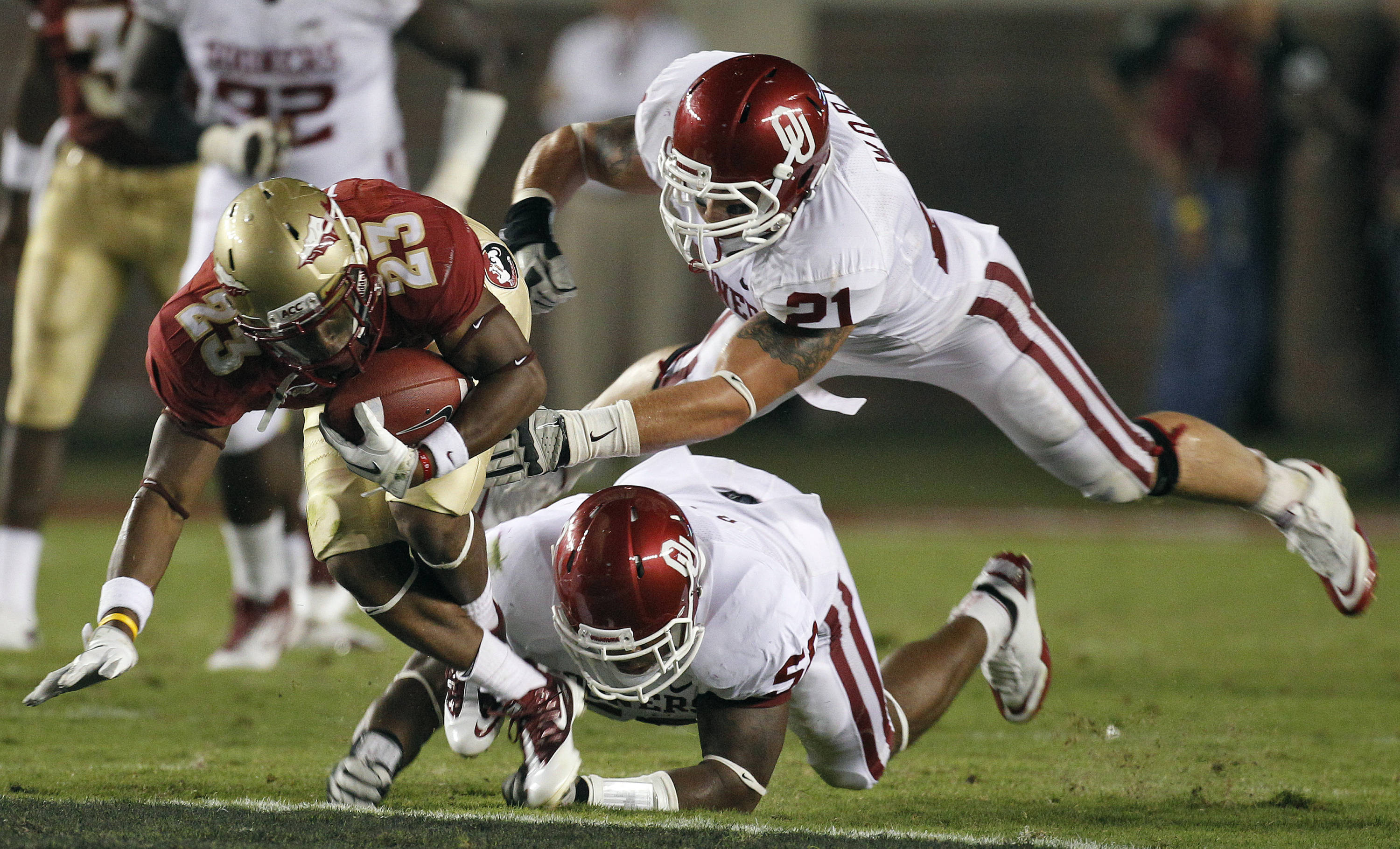Florida State running back Chris Thompson (23) eludes a tackle by Oklahoma linebacker Tom Wort (21) and defensive end Ronnell Lewis (56). (AP Photo/Chris O'Meara)