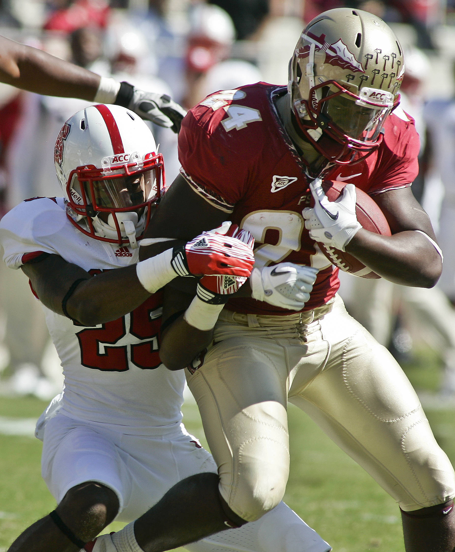 Florida State running back Lonnie Pryor (24) drags North Carolina State safety Dontae Johnson (25) as he scores on an 8-yard touchdown run in the second quarter of an NCAA college football game at Doak Campbell Stadium in Tallahassee, Fla., Saturday, Oct. 29, 2011. (AP Photo/Phil Sears)