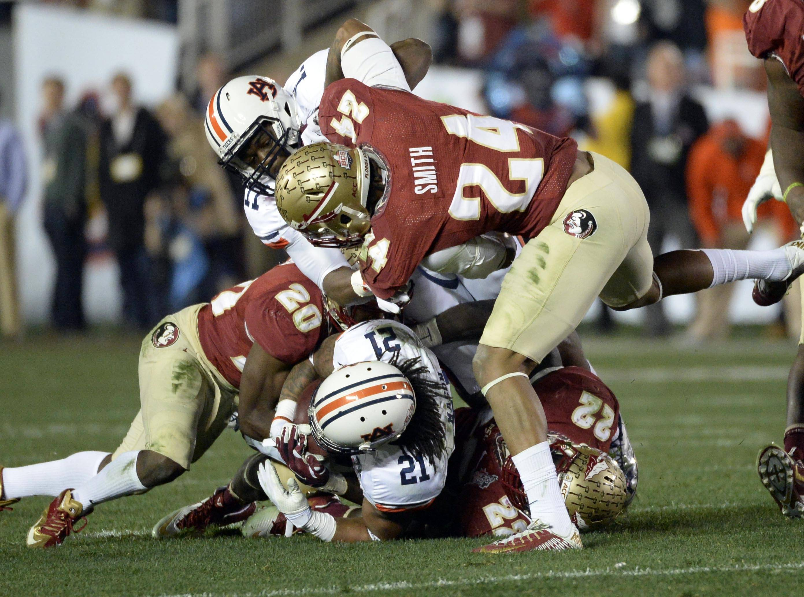 Jan 6, 2014; Pasadena, CA, USA; Florida State Seminoles defensive back Lamarcus Joyner (20) and linebacker Telvin Smith (22) and linebacker Terrance Smith (24) tackle Auburn Tigers running back Tre Mason (21) during the first half of the 2014 BCS National Championship game at the Rose Bowl.  Mandatory Credit: Richard Mackson-USA TODAY Sports