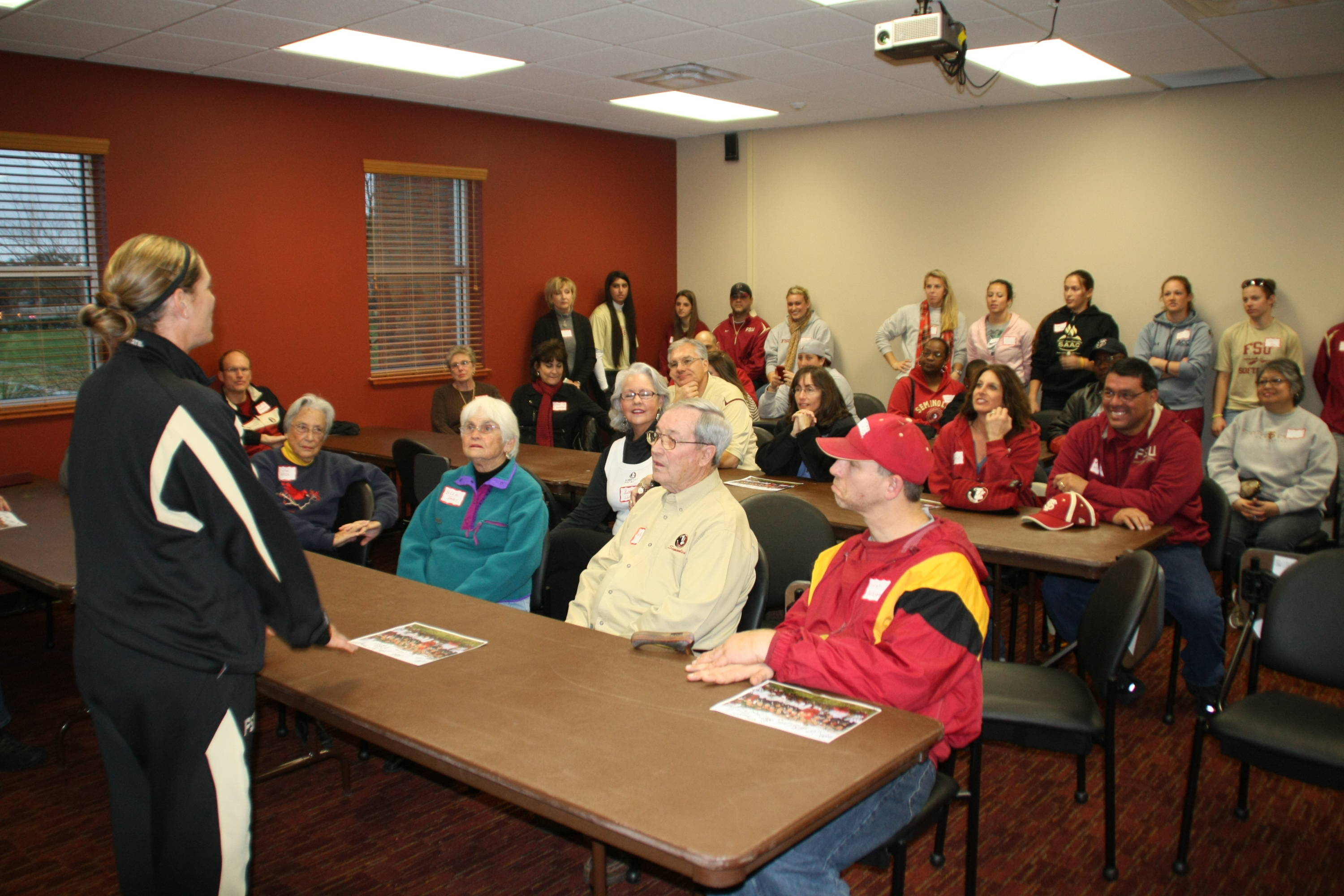Coach Alameda speaks with Dugout Club members before a function in February.