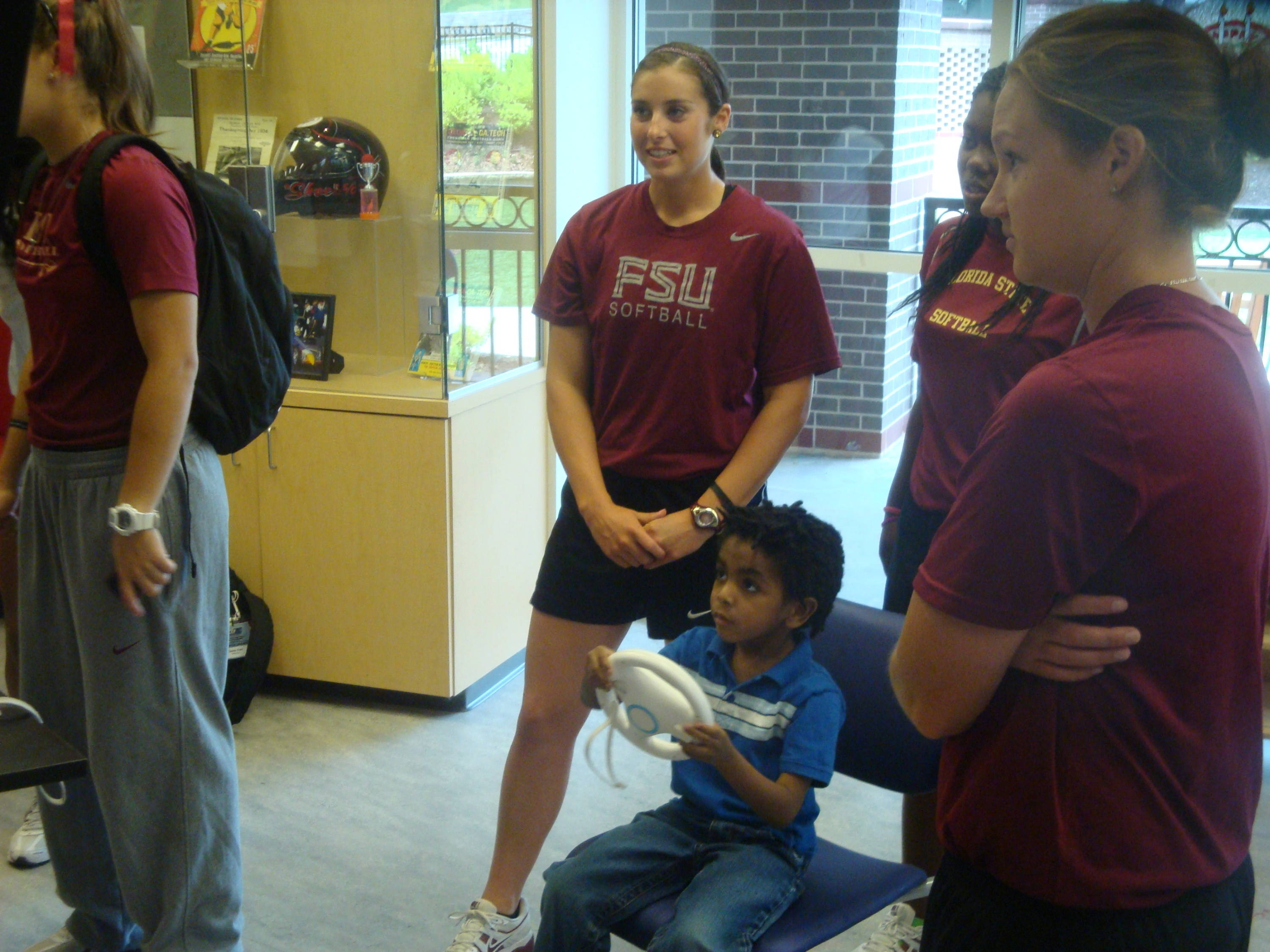 Maddie O'Brien (L), Amber Bryant (C) and Mallory Borden observe new friend Jonathan as he plays Mario Kart