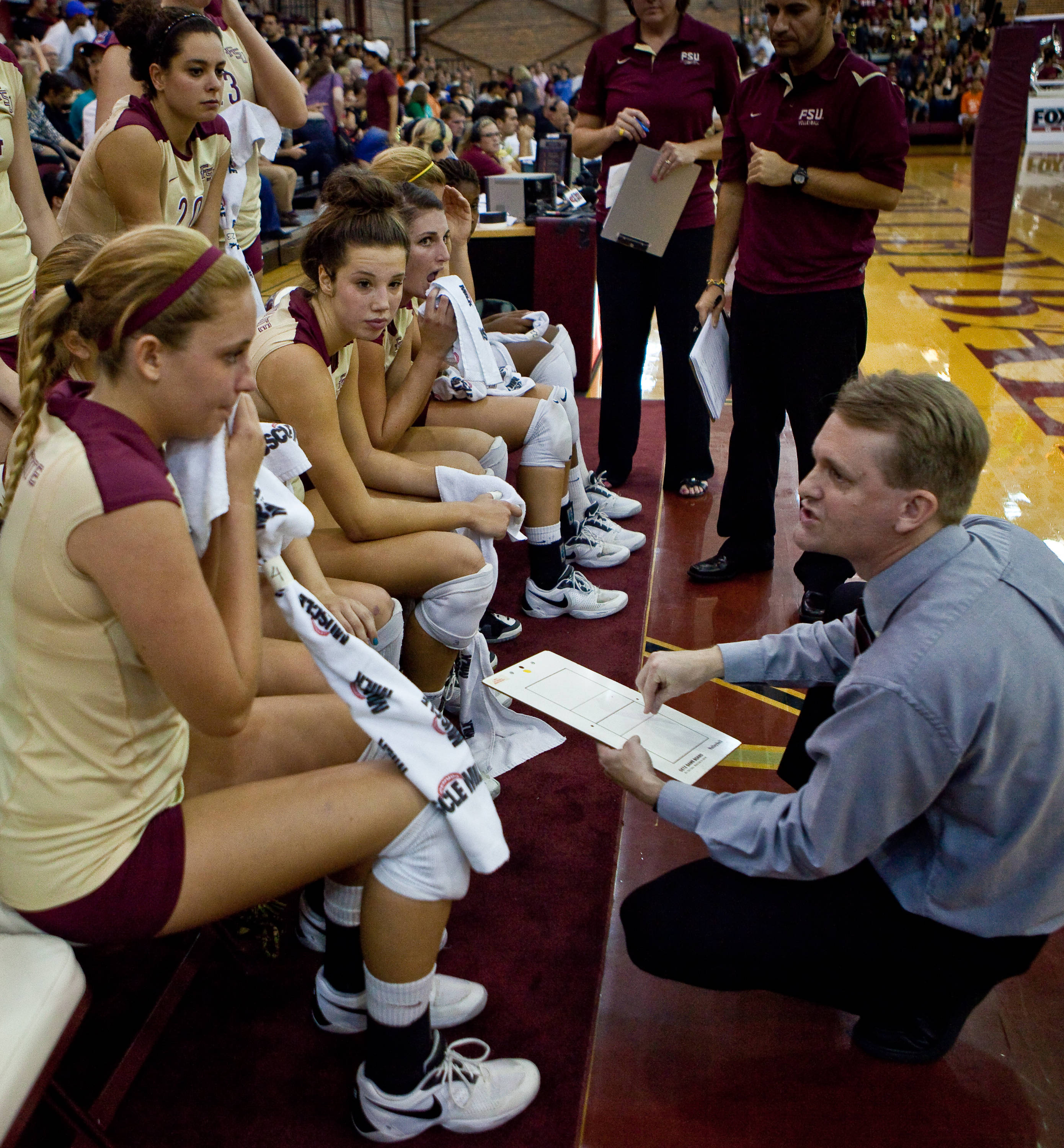 Head coach Chris Poole talks to the team during a timeout