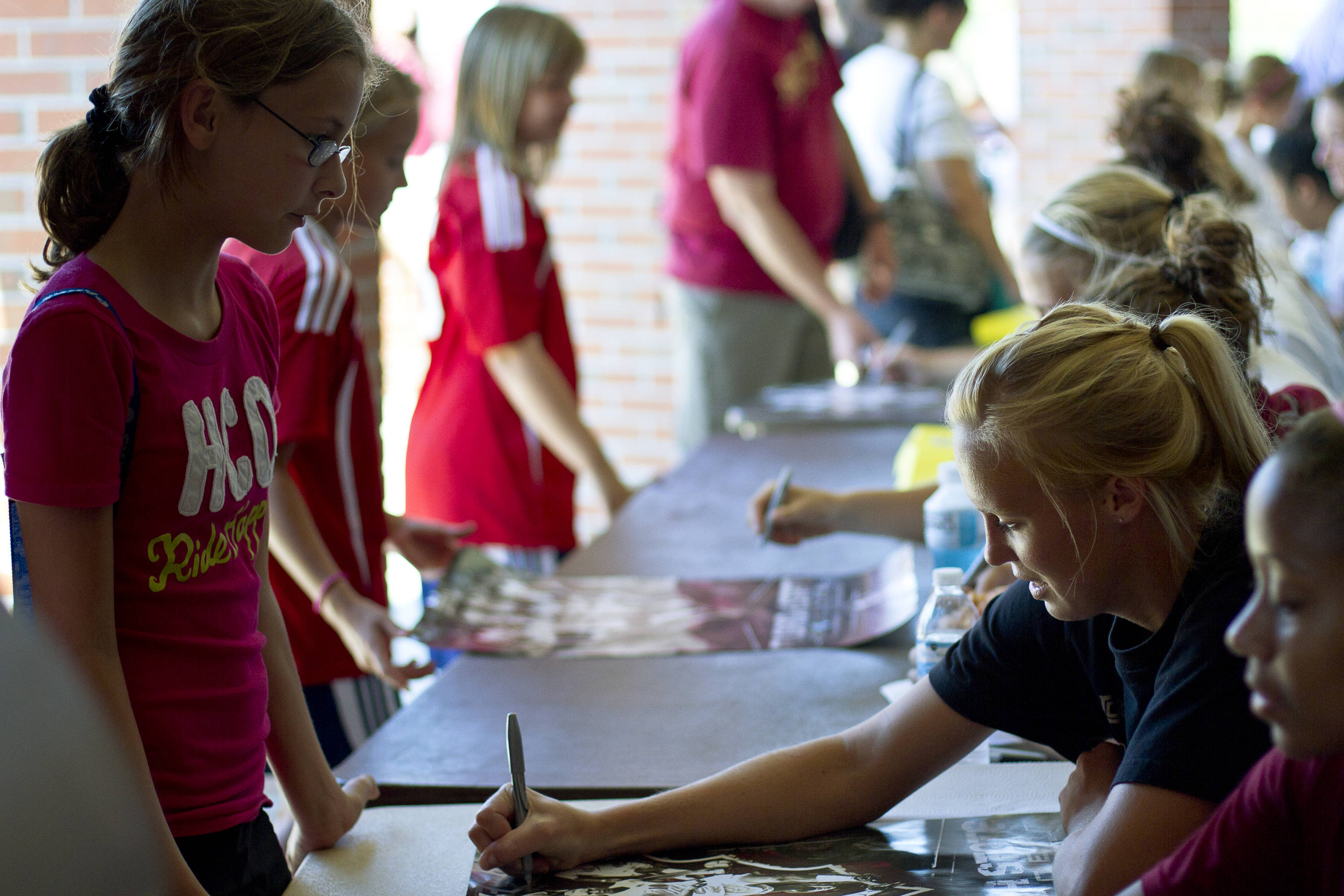 Ella Stephan (17) signs a poster for a young fan after Sunday's game against North Florida.