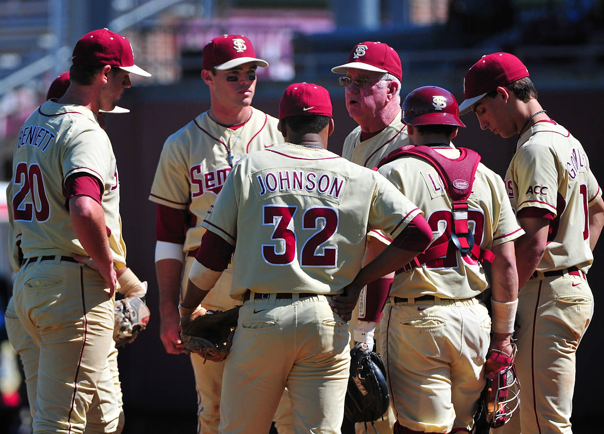 FSU coach Mike Martin holds a meeting on the mound late in the game to discuss strategy ...