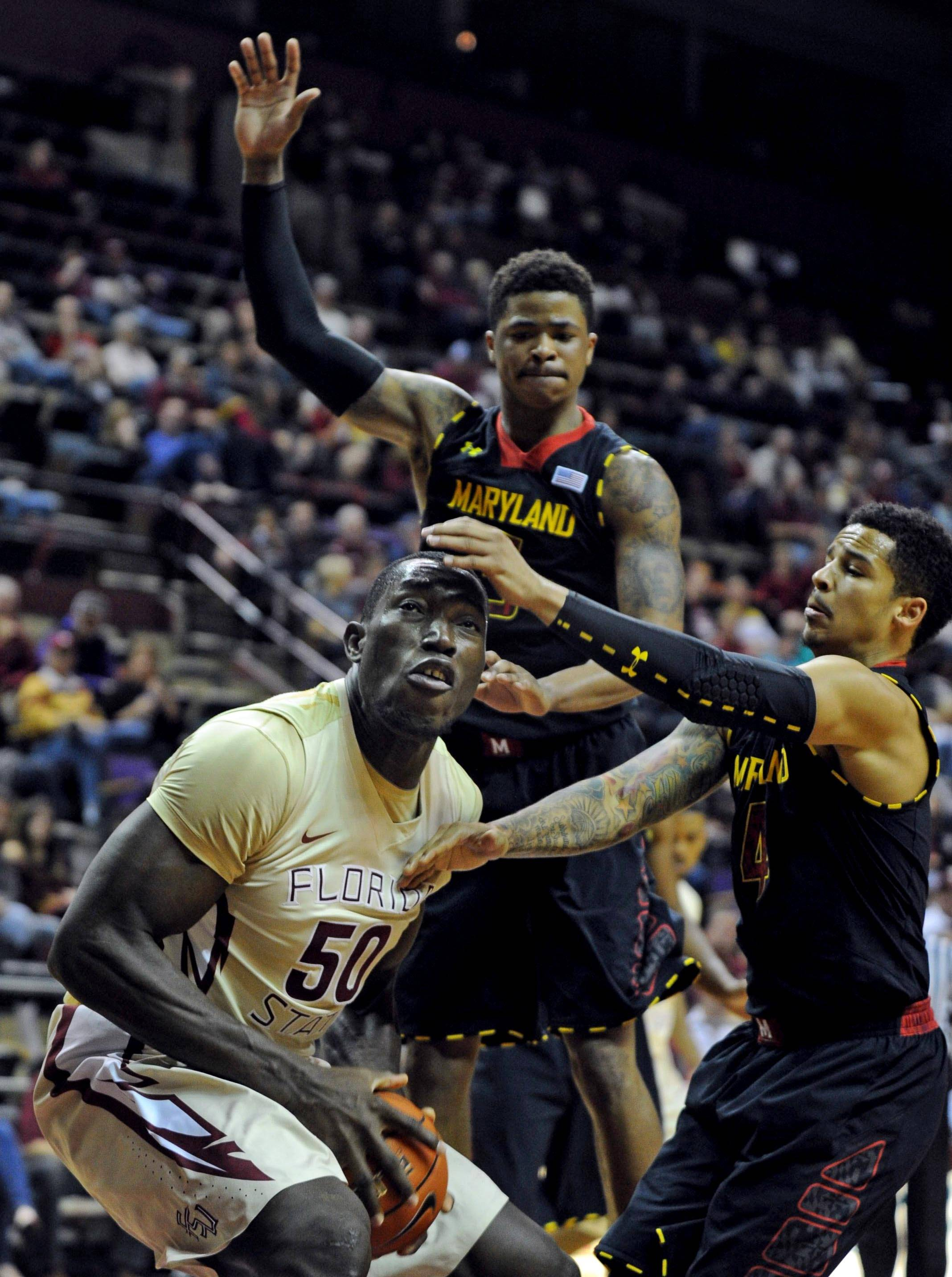 Jan 12, 2014; Tallahassee, FL, USA; Florida State Seminoles center Michael Ojo (50) looks to shoot as he is defended by Maryland Terrapins guard Seth Allen (4) and guard Nick Faust (5) during the second half at Donald L. Tucker Center. Mandatory Credit: Melina Vastola-USA TODAY Sports