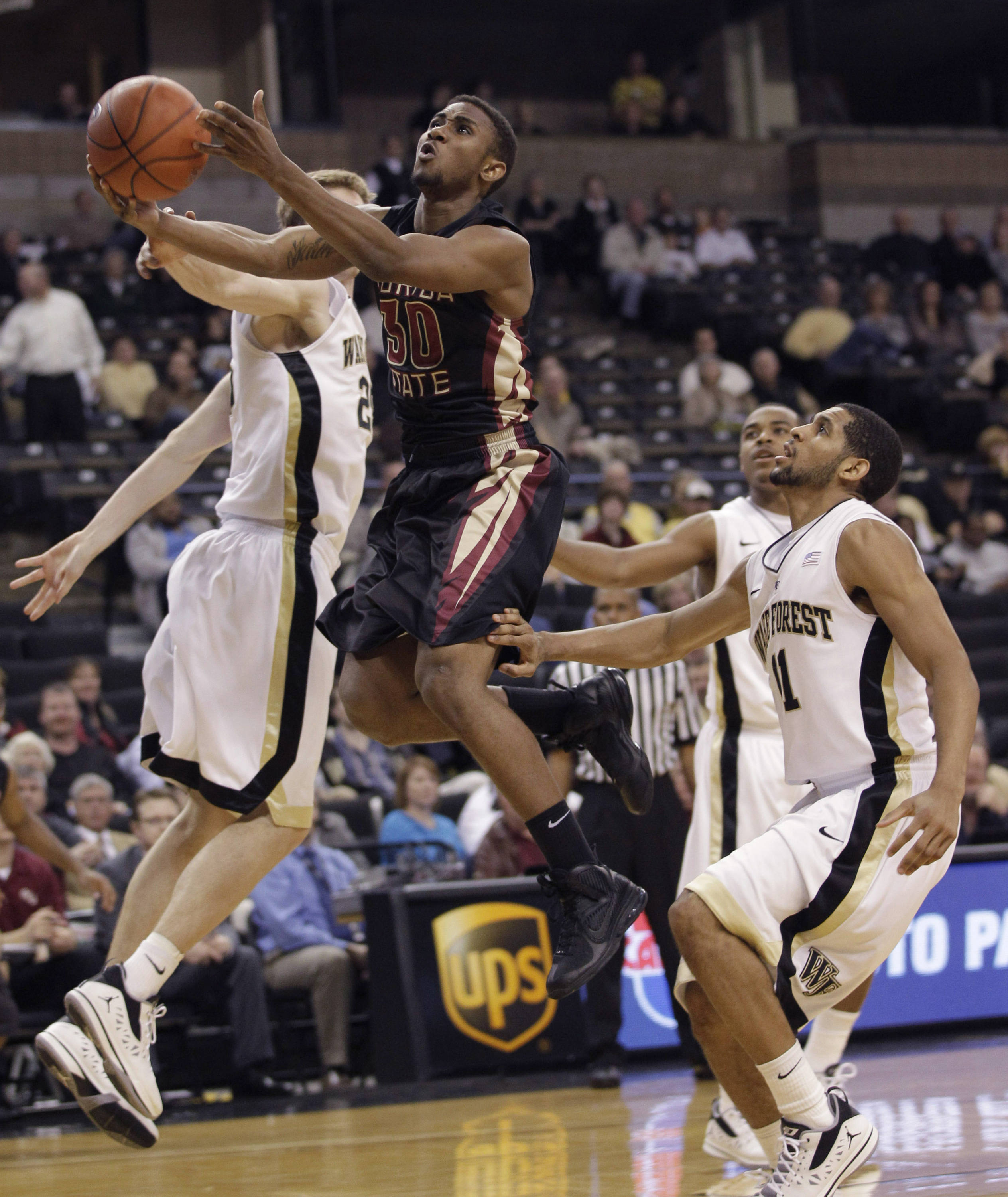 Florida State's Ian Miller drives past Wake Forest's C.J. Harris and Nikita Mescheriakov during the second half of Florida State's 75-52 win. (AP Photo/Chuck Burton)