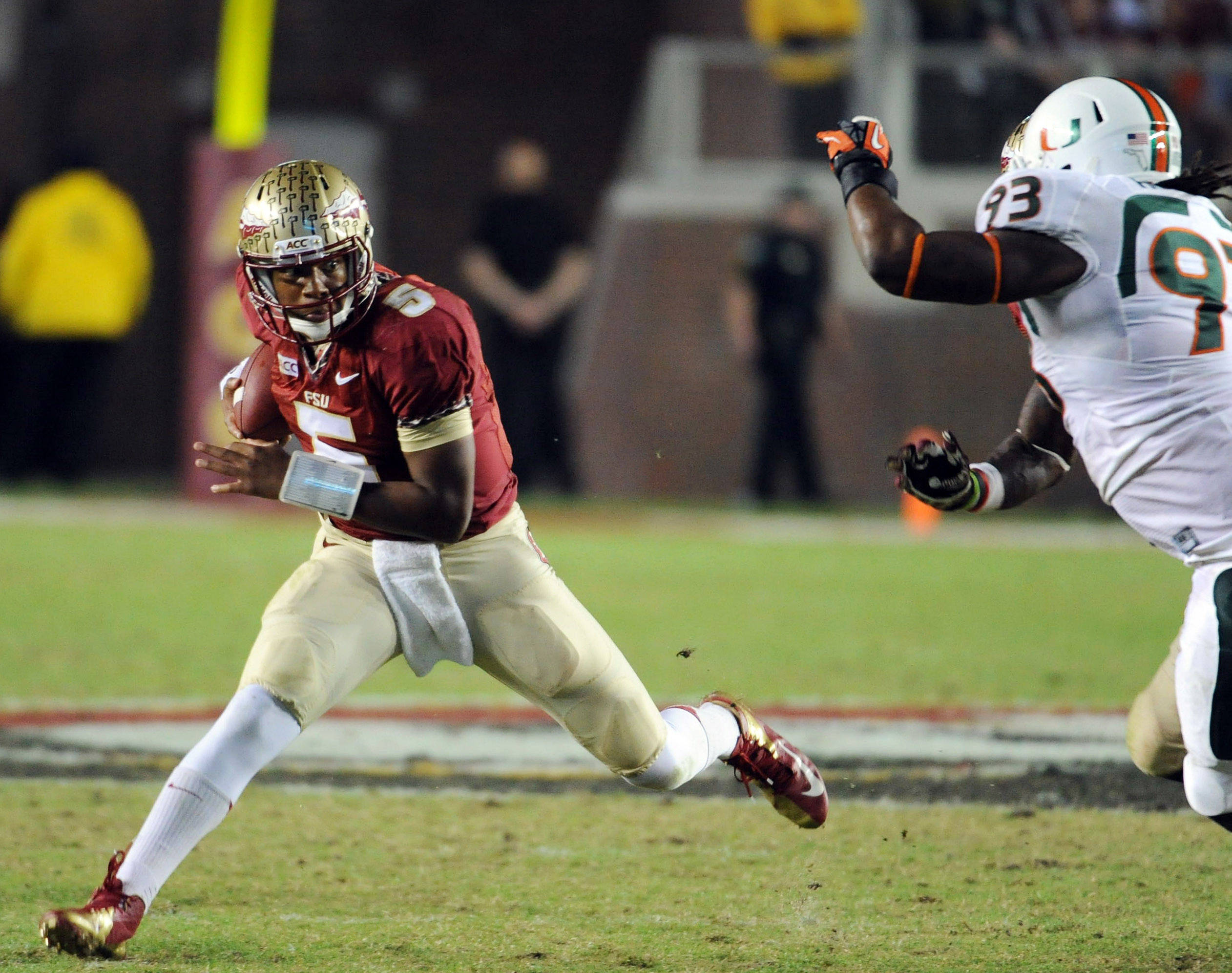 Florida State Seminoles quarterback Jameis Winston (5) makes a move to avoid Miami Hurricanes defensive lineman Luther Robinson (93) during the second half at Doak Campbell Stadium. Mandatory Credit: Melina Vastola-USA TODAY Sports