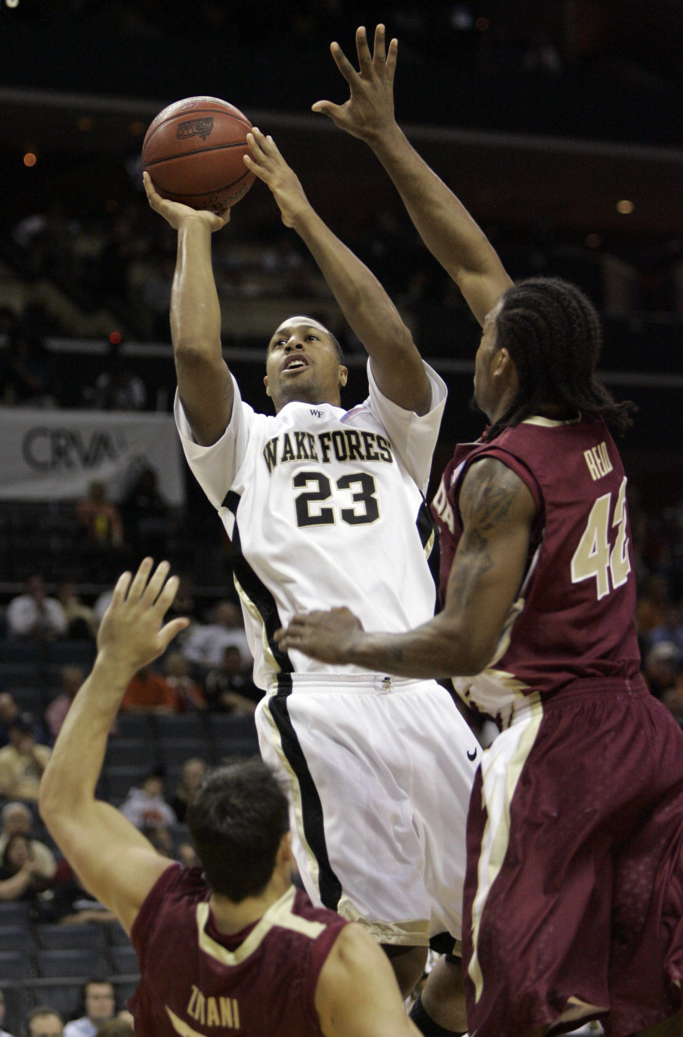 Wake Forest's James Johnson shoots over Matt Zitani, left, and Ryan Reid in the first half. (AP Photo/Gerry Broome)
