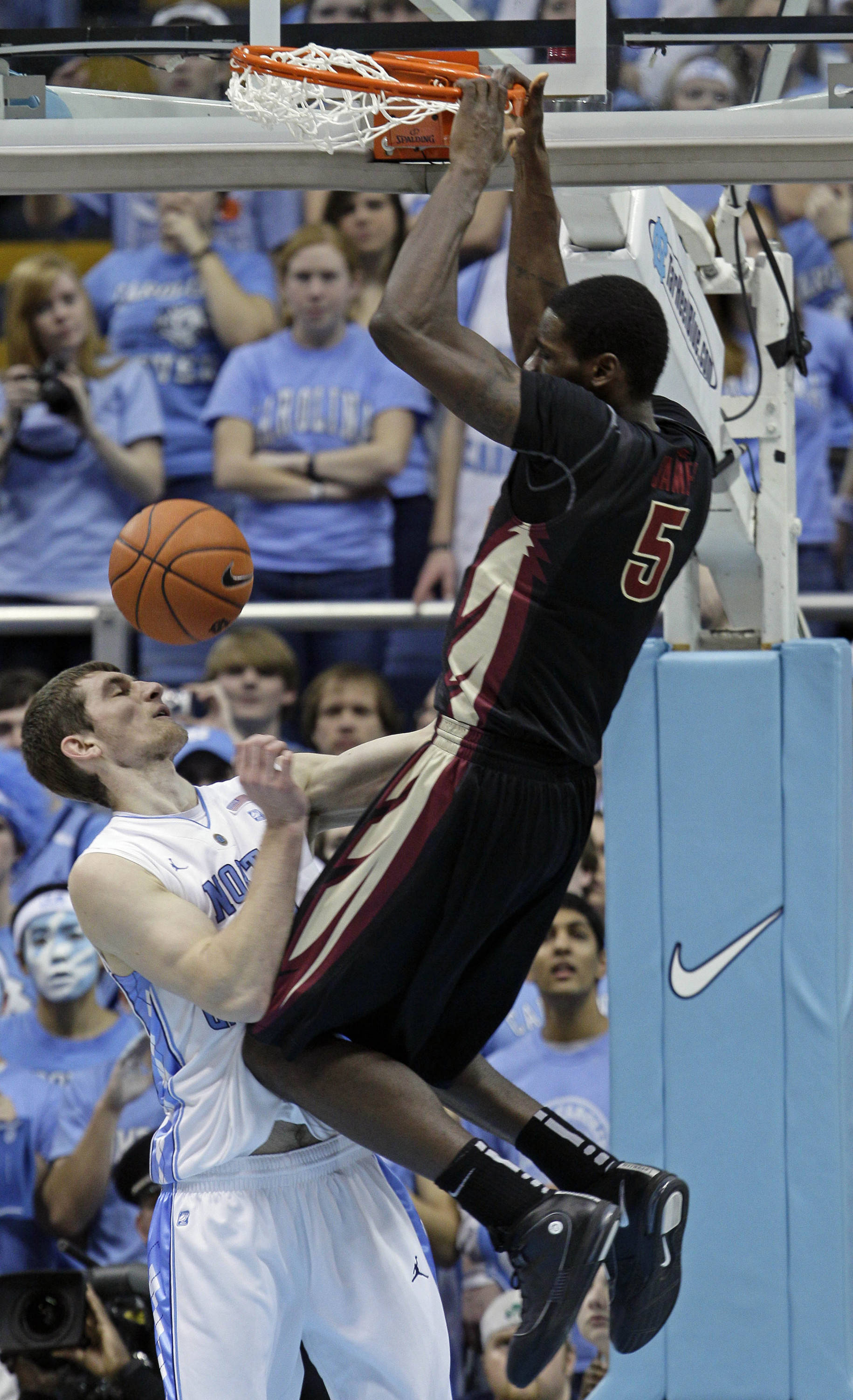 Florida State's Bernard James (5) dunks over North Carolina's Tyler Zeller during the first half of an NCAA college basketball game, Sunday, Feb. 6, 2011, in Chapel Hill, N.C. (AP Photo/Gerry Broome)