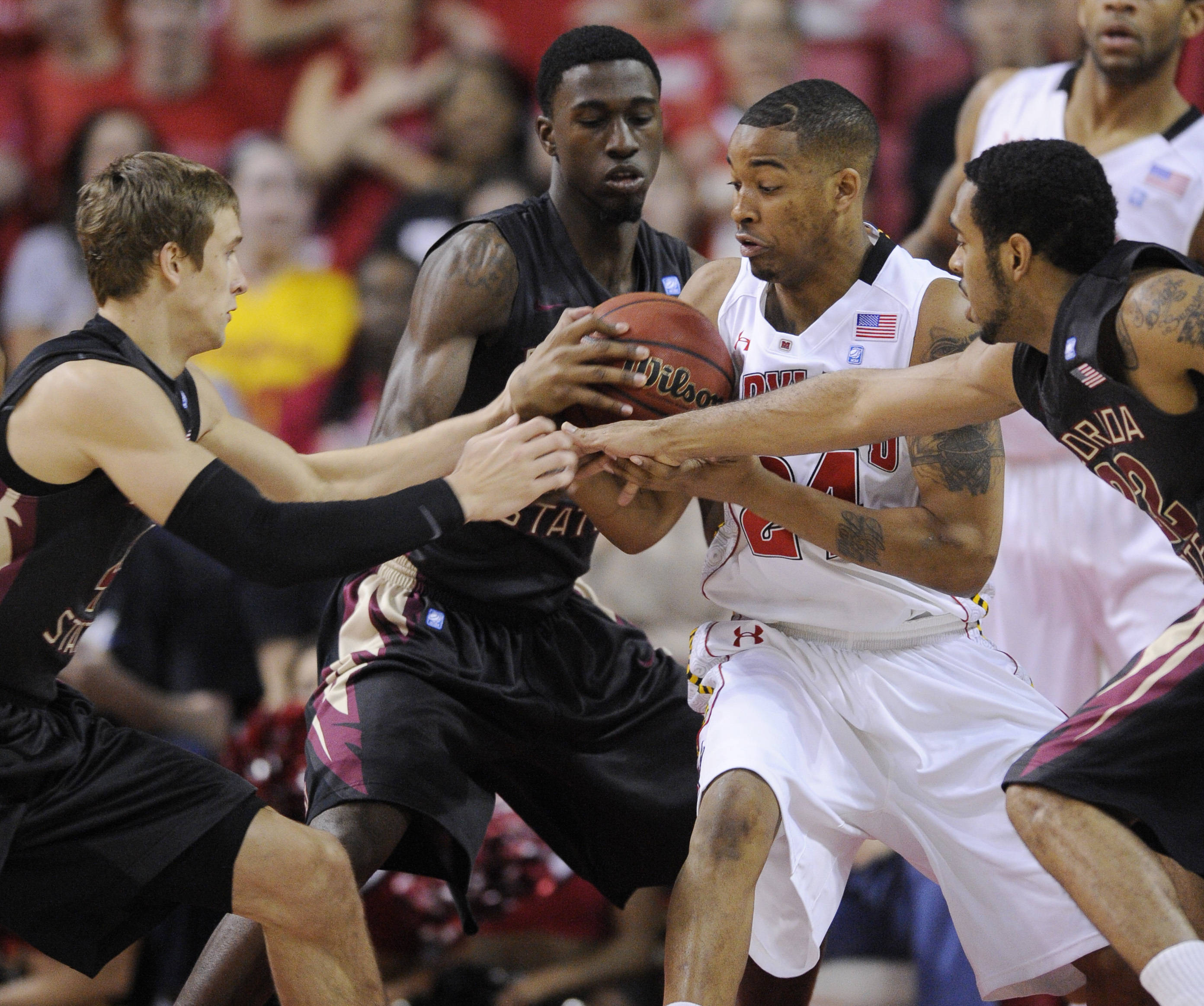 Maryland's Cliff Tucker, second from right, fights for the ball against Deividas Dulkys, left, and Derwin Kitchen, right, during the first half of an NCAA college basketball game, Wednesday, Feb. 23, 2011, in College Park, Md. (AP Photo/Nick Wass)