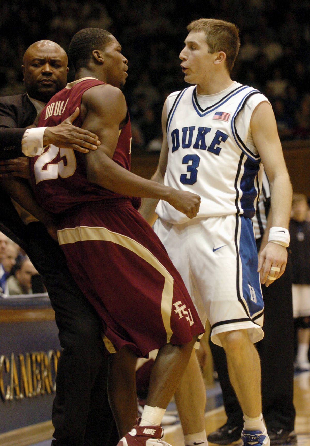 Florida State's head coach Leonard Hamilton, left, pulls his player Toney Douglas (23) away from Duke's Greg Paulus (3) as they exchange words in the second half of a basketball game in Durham, N.C., on Sunday, Feb. 4, 2007. Paulus received a foul and the Florida State bench received a technical foul. Florida State upset Duke 68-67. (AP Photo/Sara D. Davis)