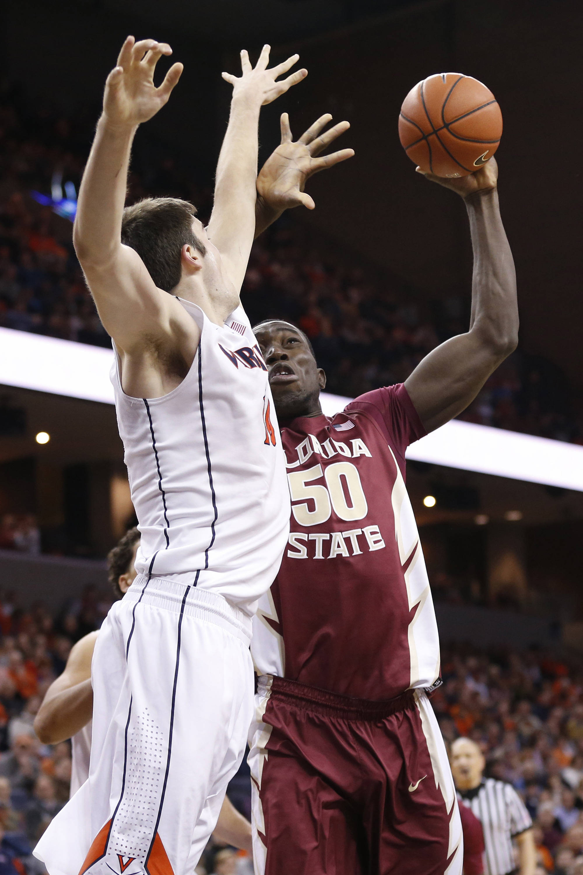 Jan 18, 2014; Charlottesville, VA, USA; Florida State Seminoles center Michael Ojo (50) shoots the ball as Virginia Cavaliers forward/center Mike Tobey (10) defends in the first half at John Paul Jones Arena. Mandatory Credit: Geoff Burke-USA TODAY Sports