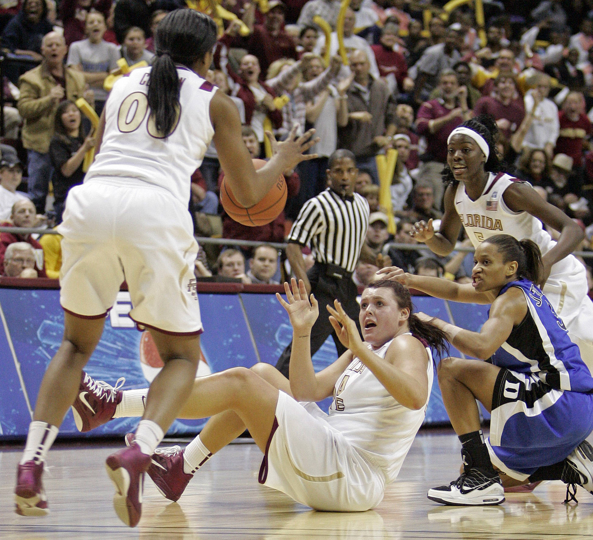 Florida State's Cierra Bravard, center, passes to teammate Chasity Clayton, left, after fighting with Duke's Jasmine Thomas, front right, for a loose ball in the second half of an NCAA college basketball game which Duke won 87-70  on Friday, Jan. 14, 2011, in Tallahassee, Fla. (AP Photo/Steve Cannon)