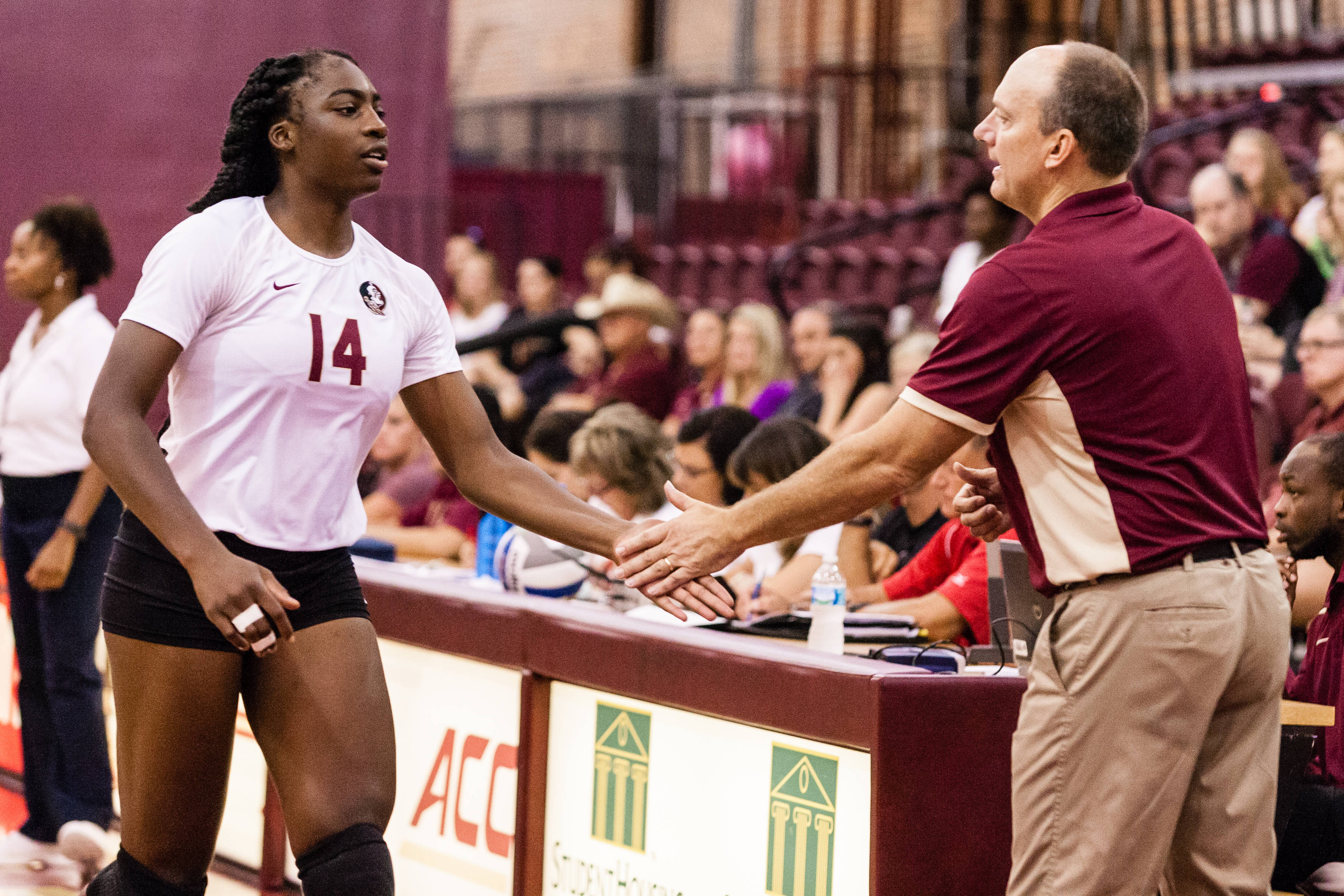 Mercedes Vaughn comes off the floor and is greeted by Coach Hulsmeyer