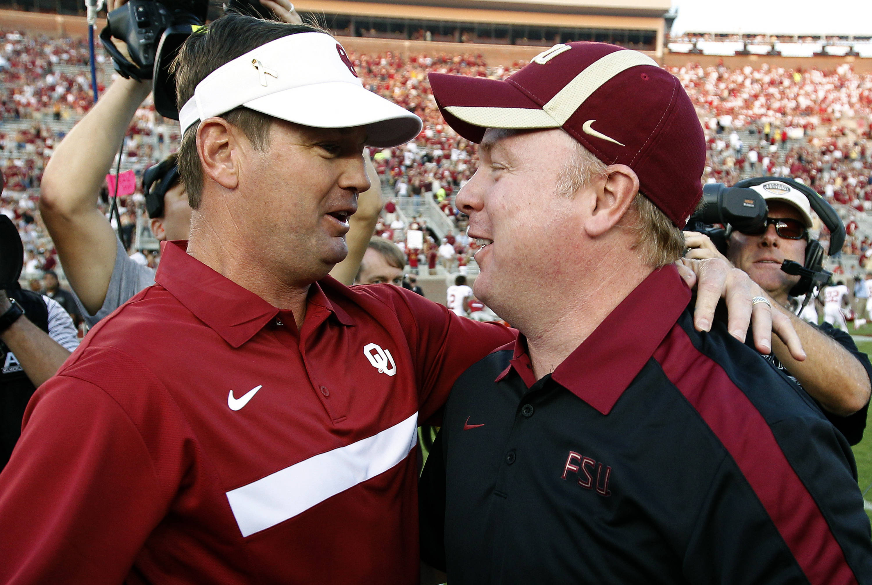 Oklahoma head coach Bob Stoops, left, hugs his brother, Florida State defensive coordinator Mark Stoops before the game. (AP Photo/Chris O'Meara)