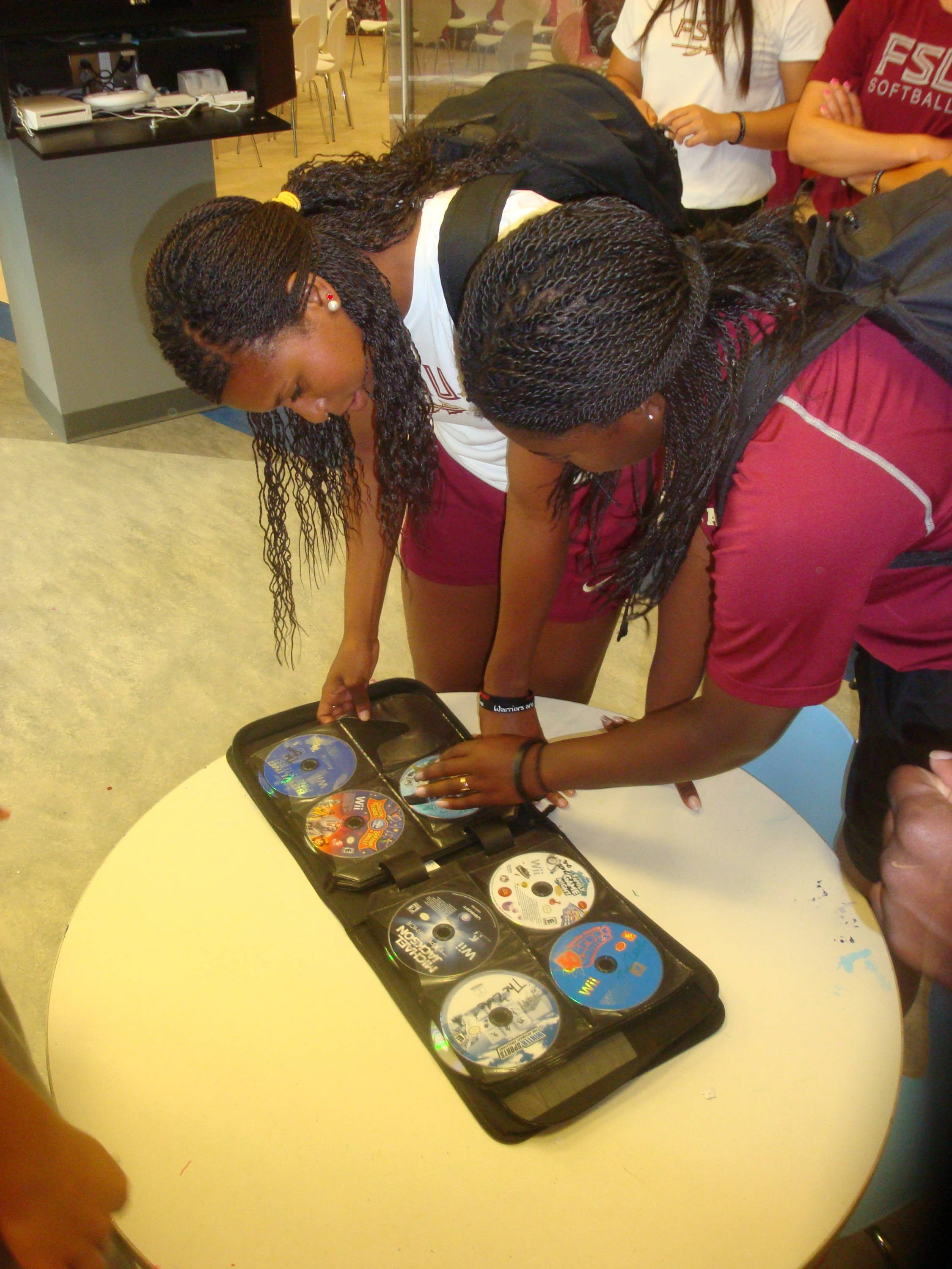 Tiffani Brown and Morgan Bullock decide which Nintendo Wii games they will play with the children