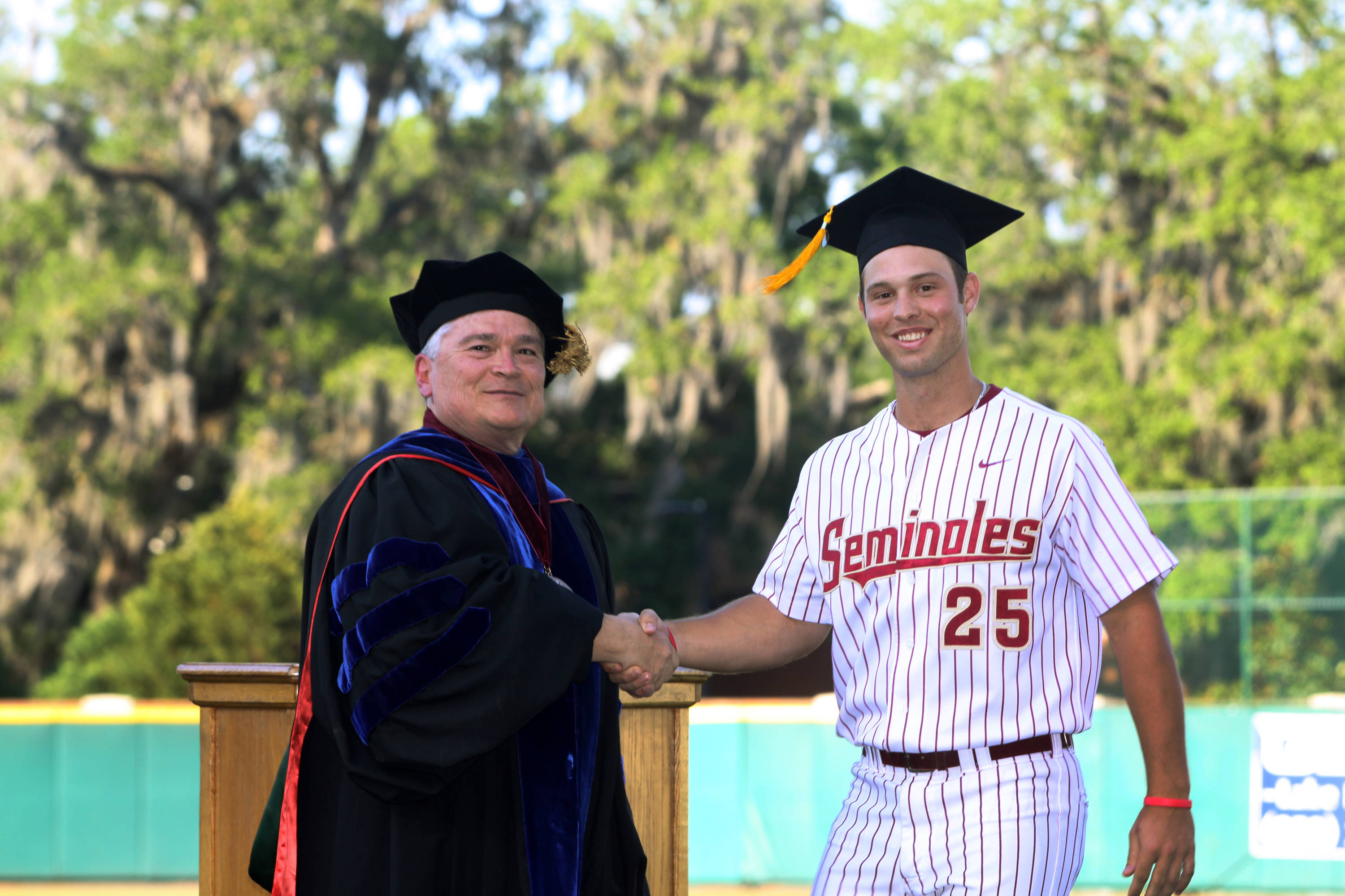 2011 Spring Graduation Ceremony held at Dick Howser Stadium to honor the graduating baseball seniors. Mike McGee (25) with President Barron