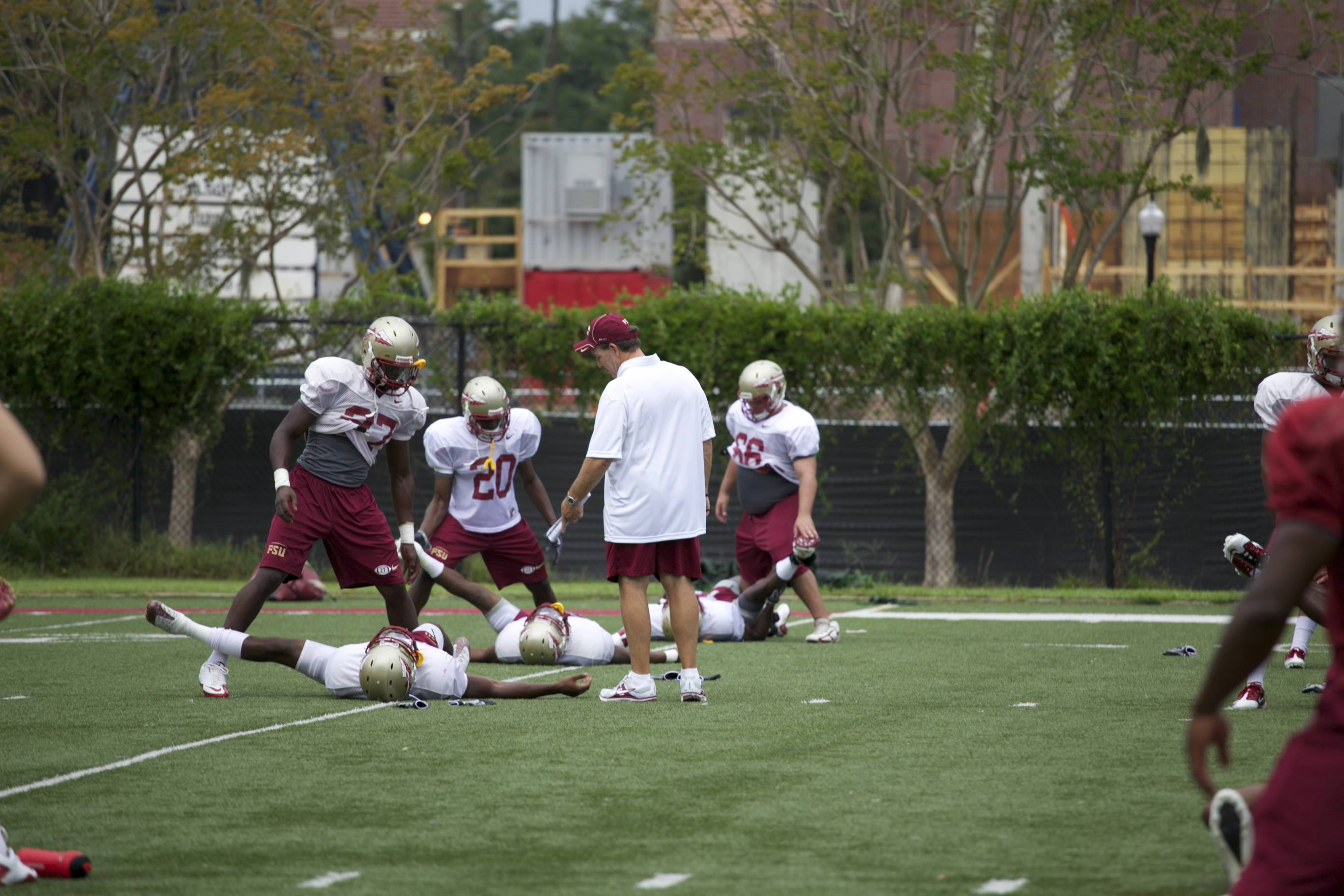 Coach Fisher helping the boys stretch before practice