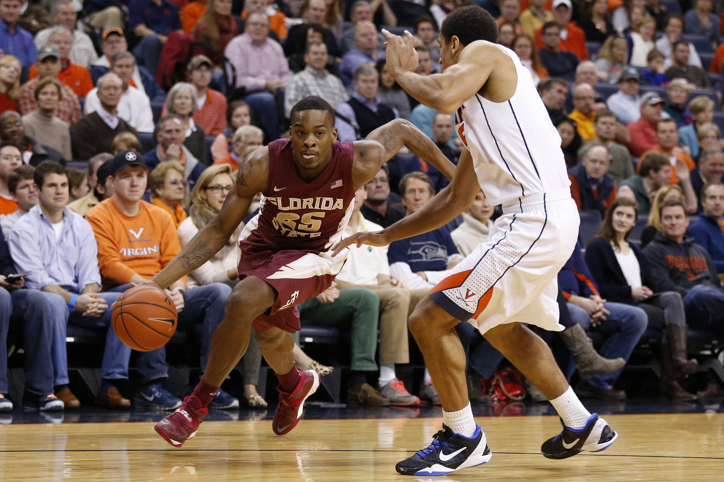 Jan 18, 2014; Charlottesville, VA, USA; Florida State Seminoles guard Aaron Thomas (25) dribbles the ball around Virginia Cavaliers guard Malcolm Brogdon (15) in the first half at John Paul Jones Arena. Mandatory Credit: Geoff Burke-USA TODAY Sports