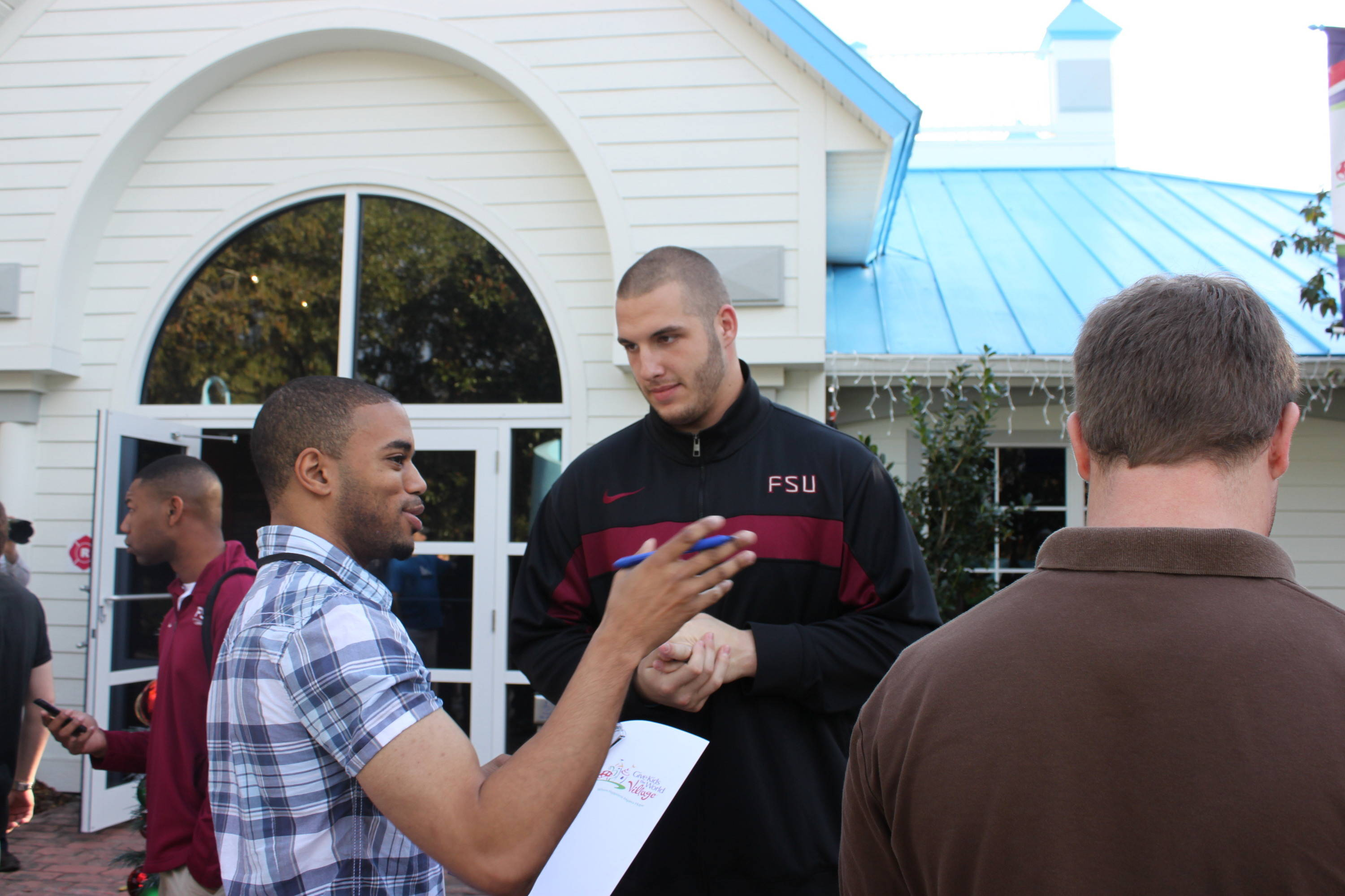 Defensive end Bjoern Werner tells a media member about the importance of sharing the day with young people.