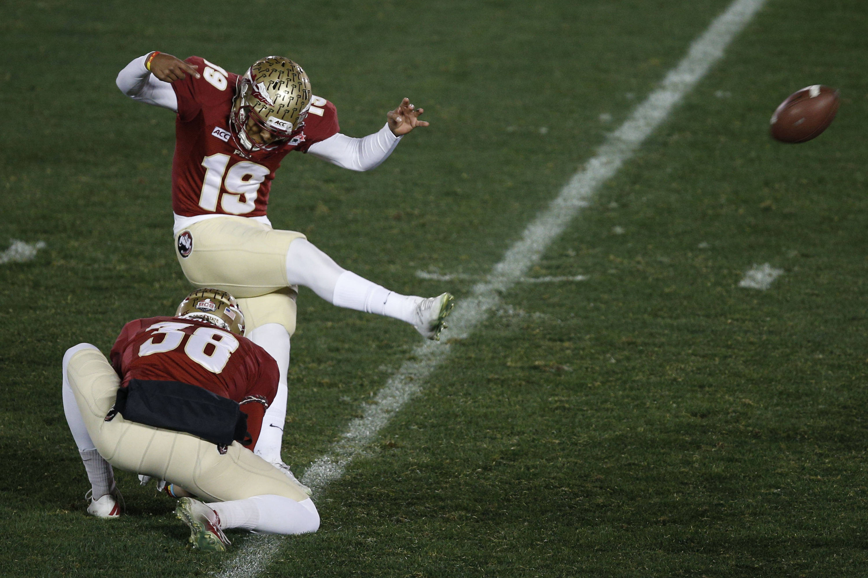 Jan 6, 2014; Pasadena, CA, USA; Florida State Seminoles kicker Roberto Aguayo (19) kicks the ball out of the hold by punter Cason Beatty (38) during the second half of the 2014 BCS National Championship game against the Auburn Tigers at the Rose Bowl.  Mandatory Credit: Kelvin Kuo-USA TODAY Sports