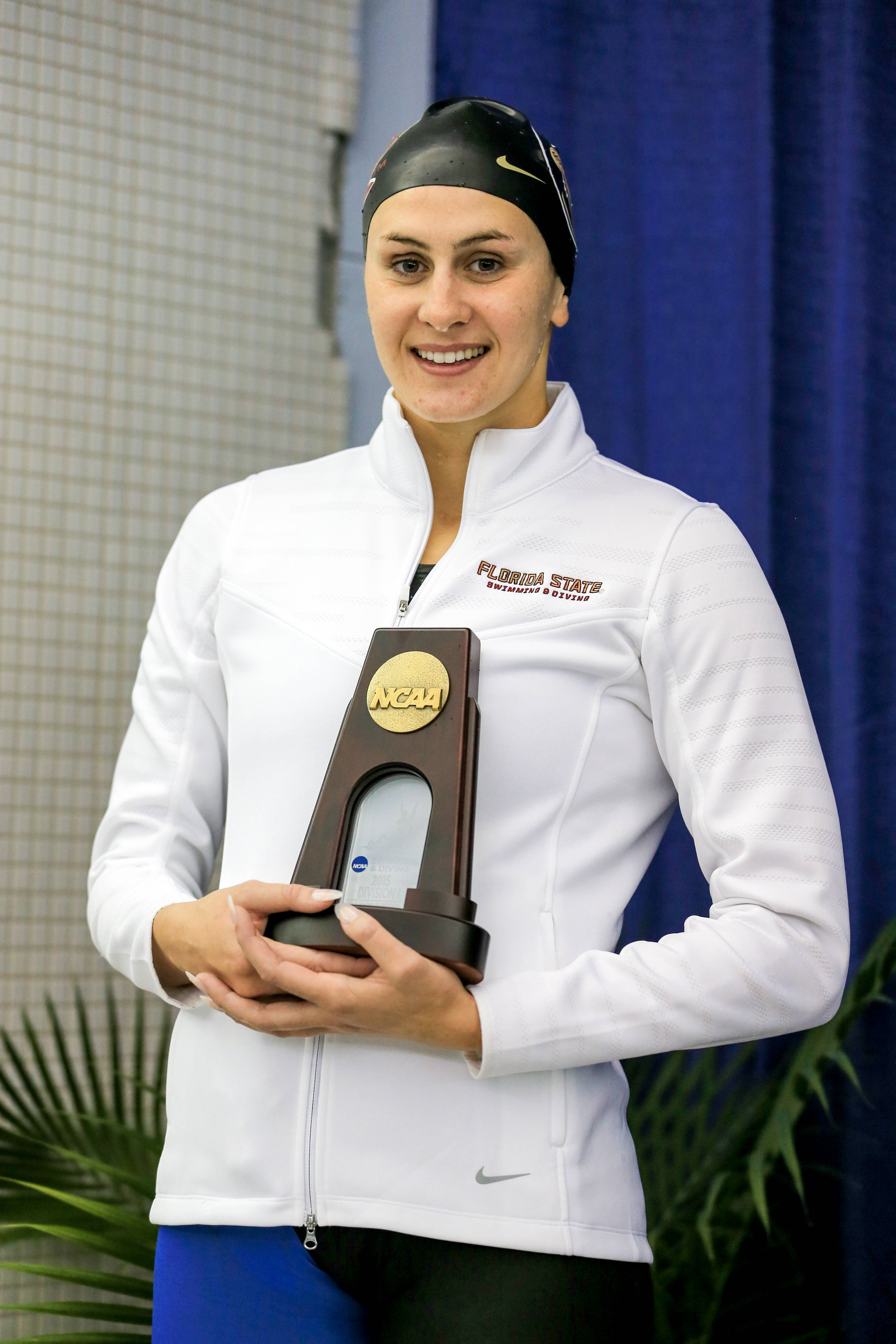 Chelsea Britt smiles on the podium of 100 fly