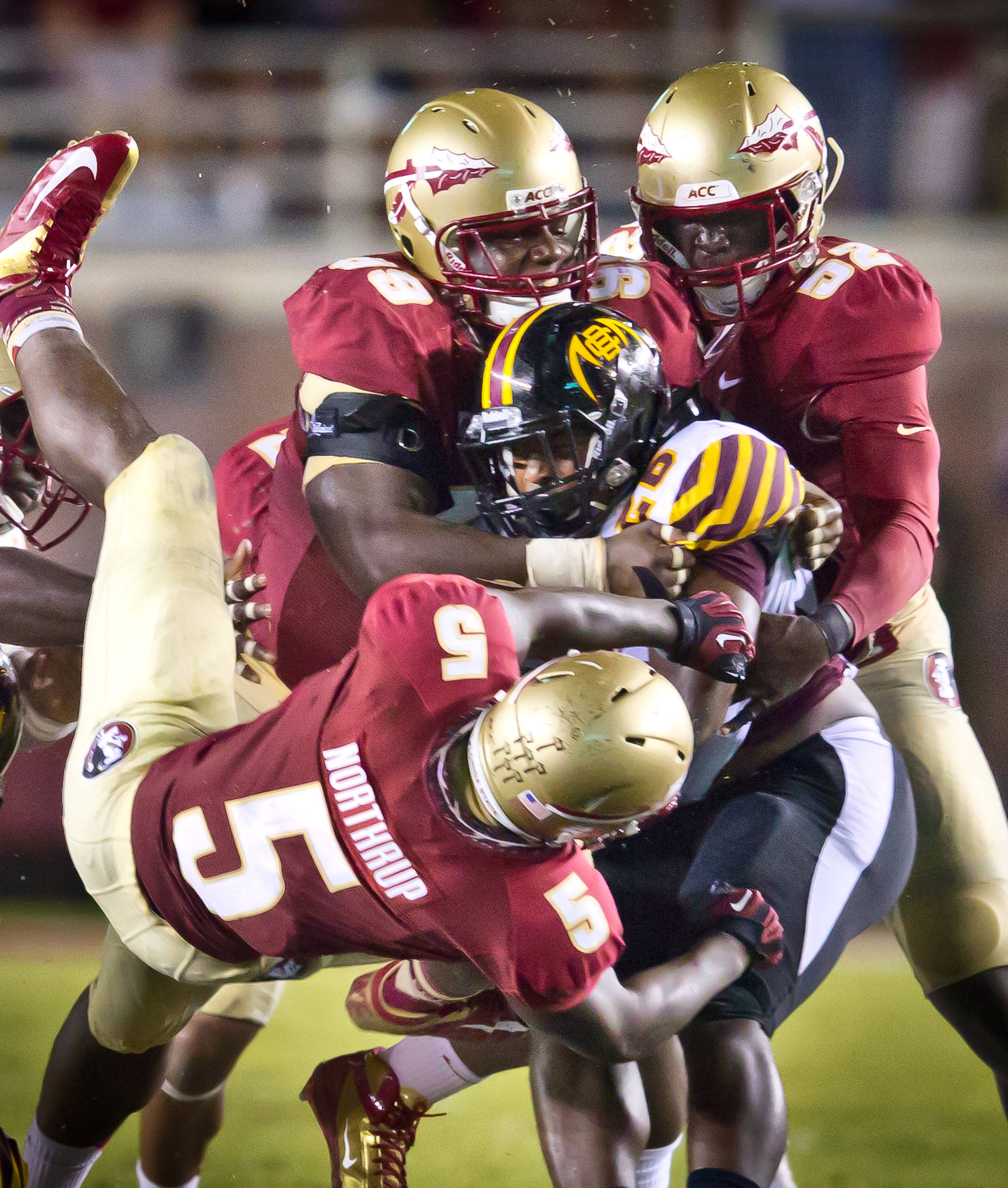 Nile Lawrence-Stample (99), Ukeme Eligwe (52), and Reggie Northrup (5) make the defensive stop.