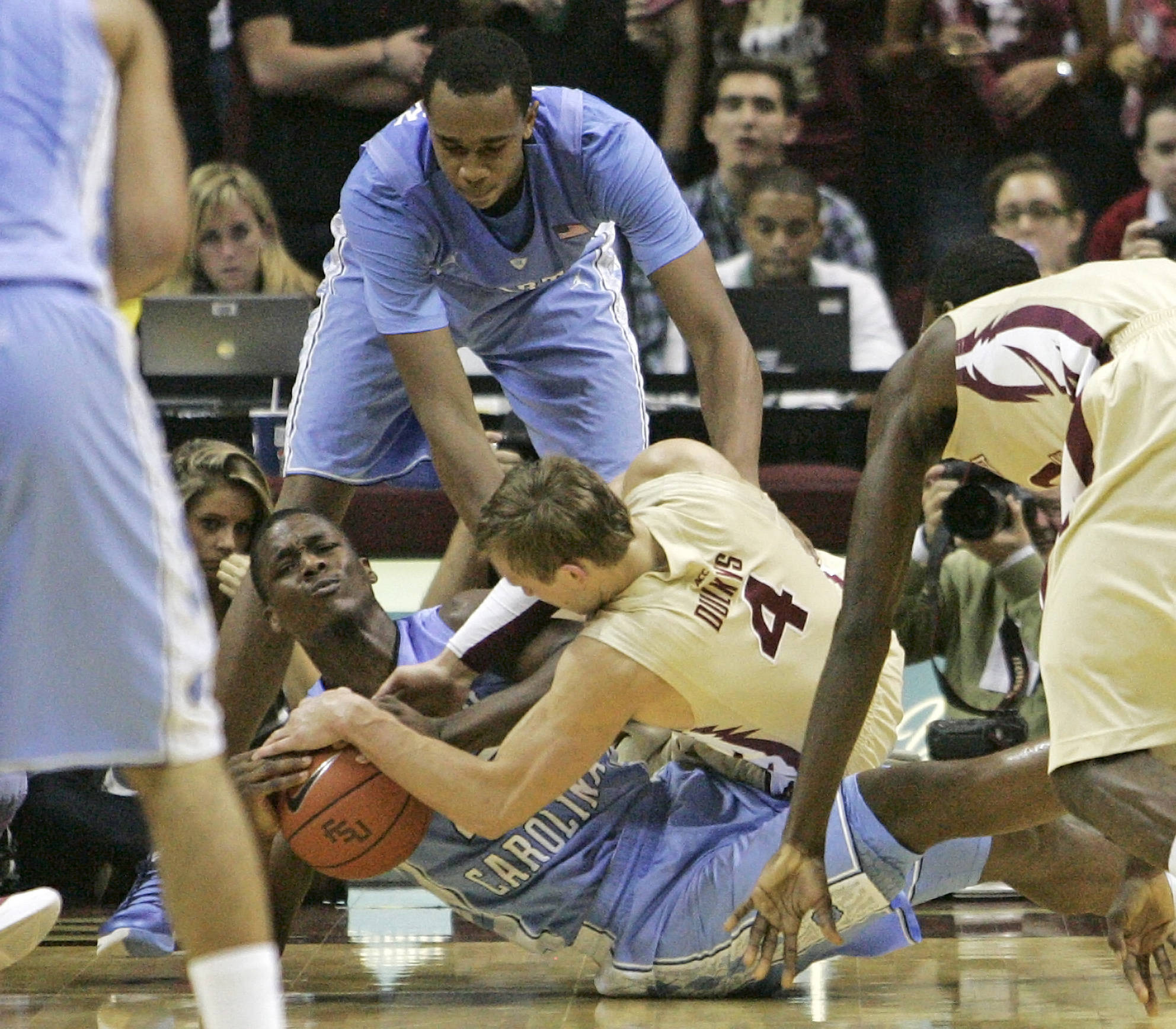 Florida State's Deividas Dulkys (4) fights North Carolina's Harrison Barnes for a loose ball as Barnes teammate John Henson tries to help out during the second half of an NCAA college basketball game,  Saturday, Jan. 14, 2012, in Tallahassee, Fla.(AP Photo/Steve Cannon)