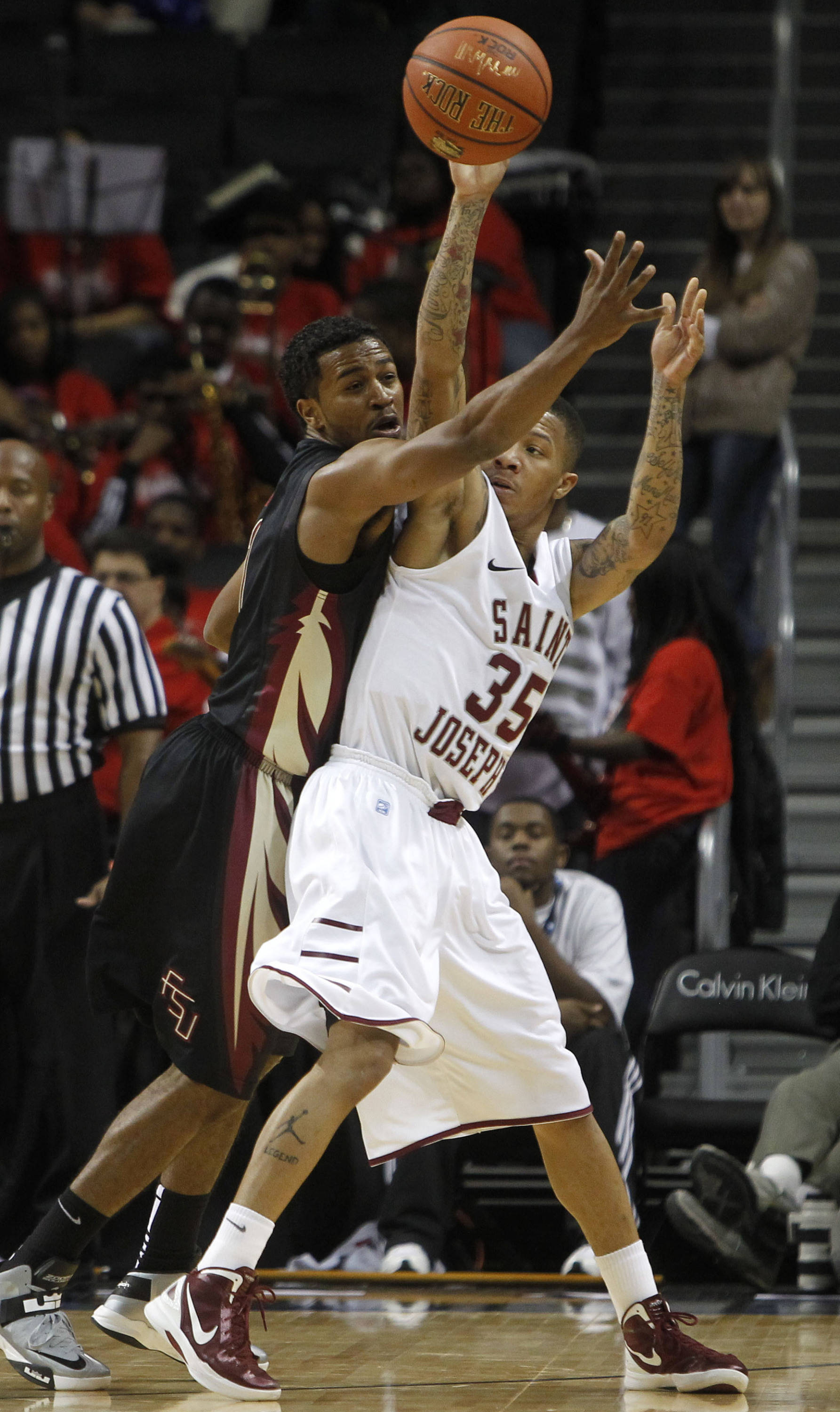 Saint Joseph's Carl Jones (35) looks to pass away from Florida State's Devon Bookert during the first half. (AP Photo/Jason DeCrow)
