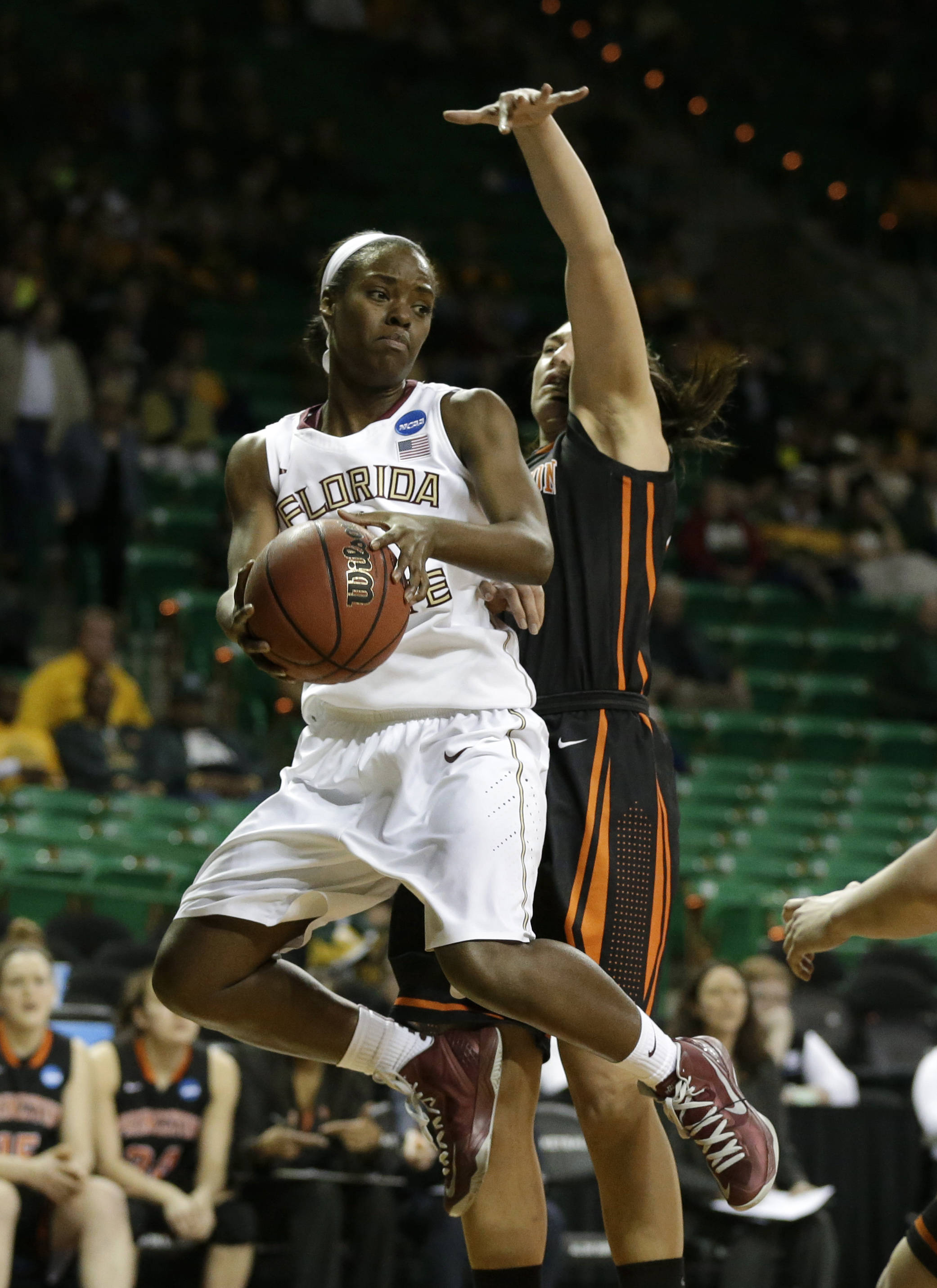 Florida State guard Morgan Jones, left, prepares to pass the ball beneath the basket as Princeton forward Kristen Helmstetter, right, defends. (AP Photo/Tony Gutierrez)