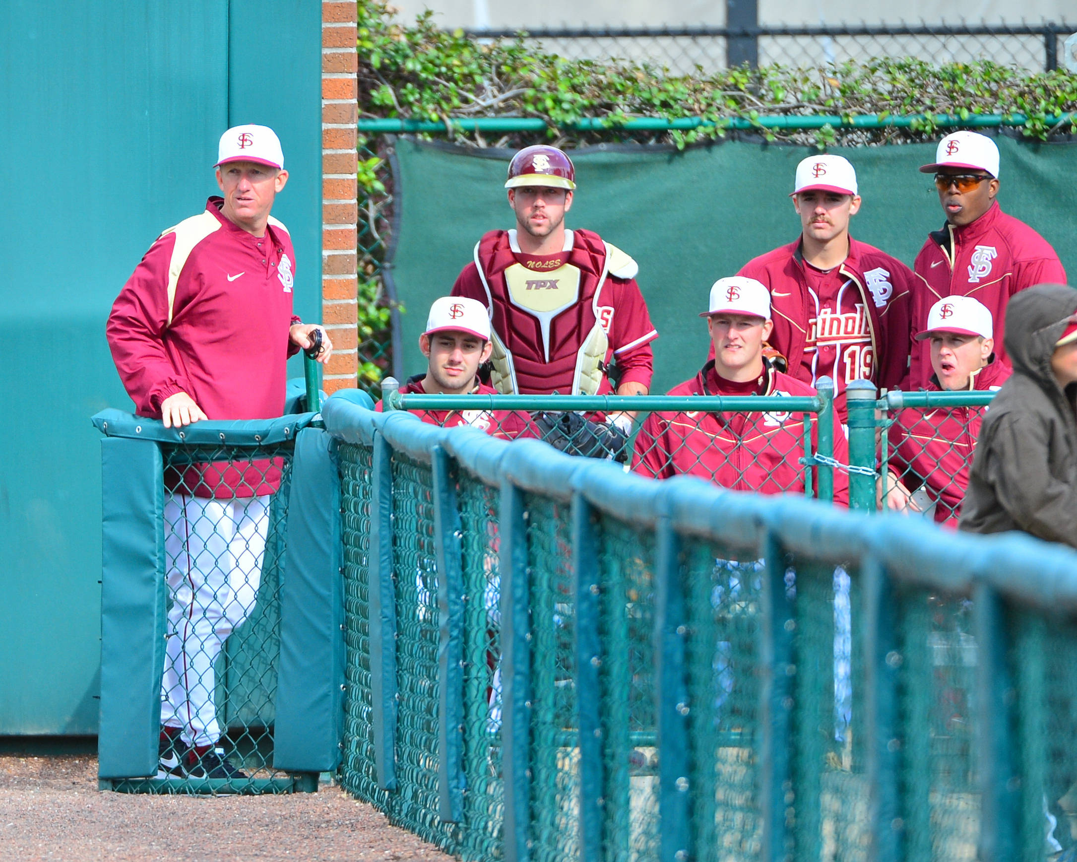 Associate head coach Mike Bell looks on from the bullpen with members of the Seminole pitching staff.
