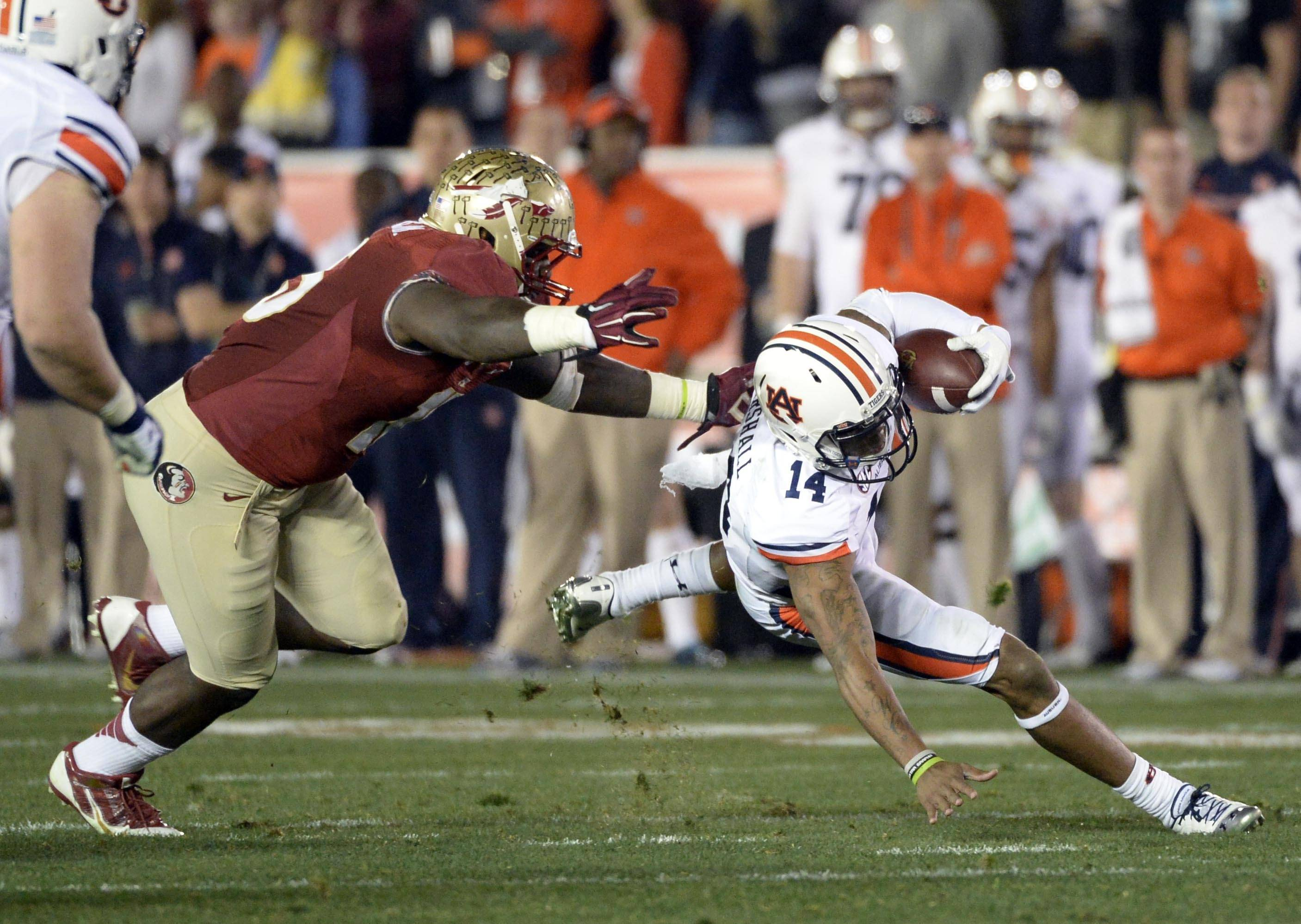 Jan 6, 2014; Pasadena, CA, USA; Florida State Seminoles defensive end Mario Edwards Jr. (15) tackles Auburn Tigers quarterback Nick Marshall (14) during the first half of the 2014 BCS National Championship game at the Rose Bowl.  Mandatory Credit: Richard Mackson-USA TODAY Sports