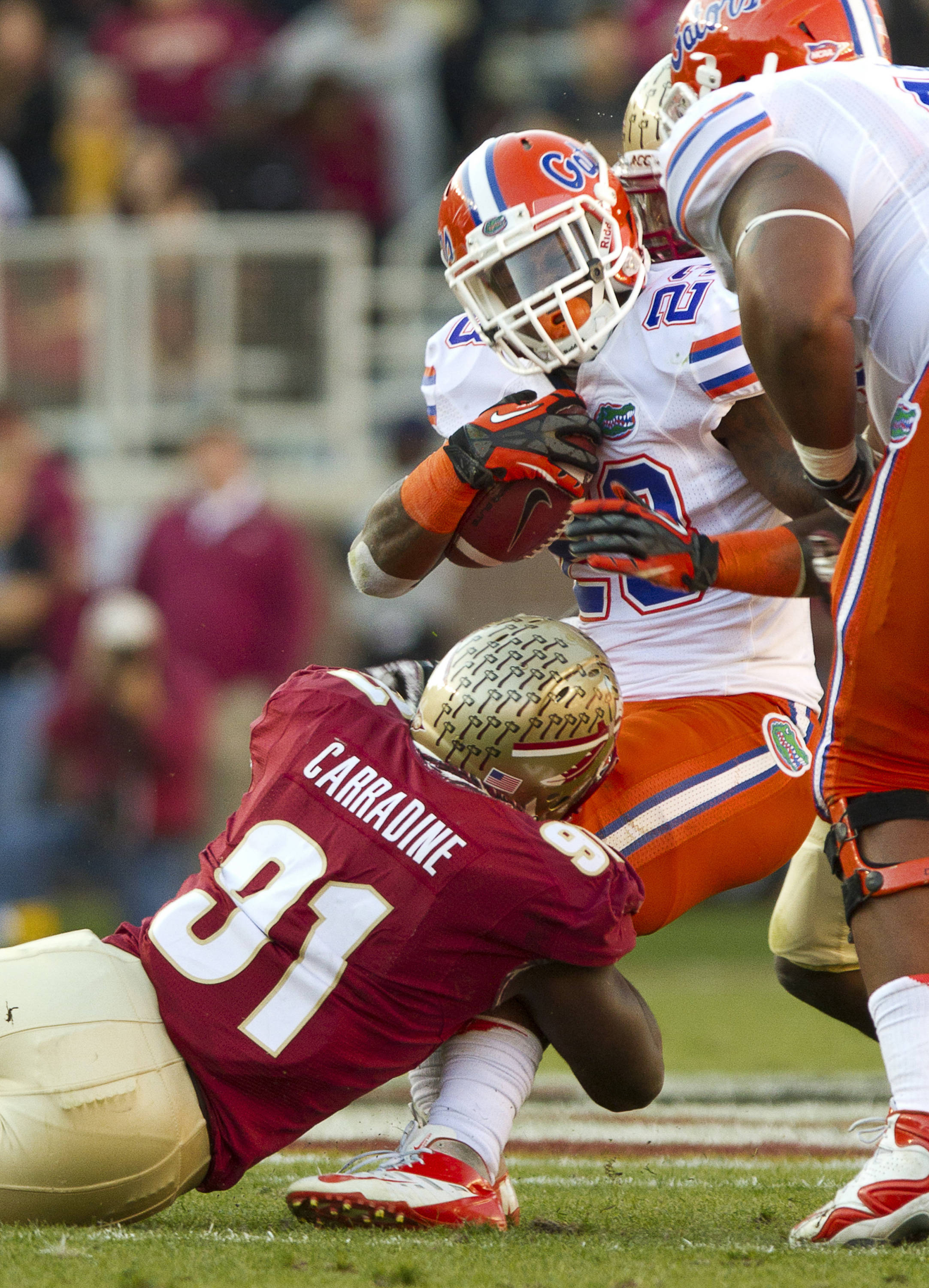 Cornellius Carradine (91) makes a tackle during FSU Football's game against UF on Saturday, November 24, 2012 in Tallahassee, Fla.