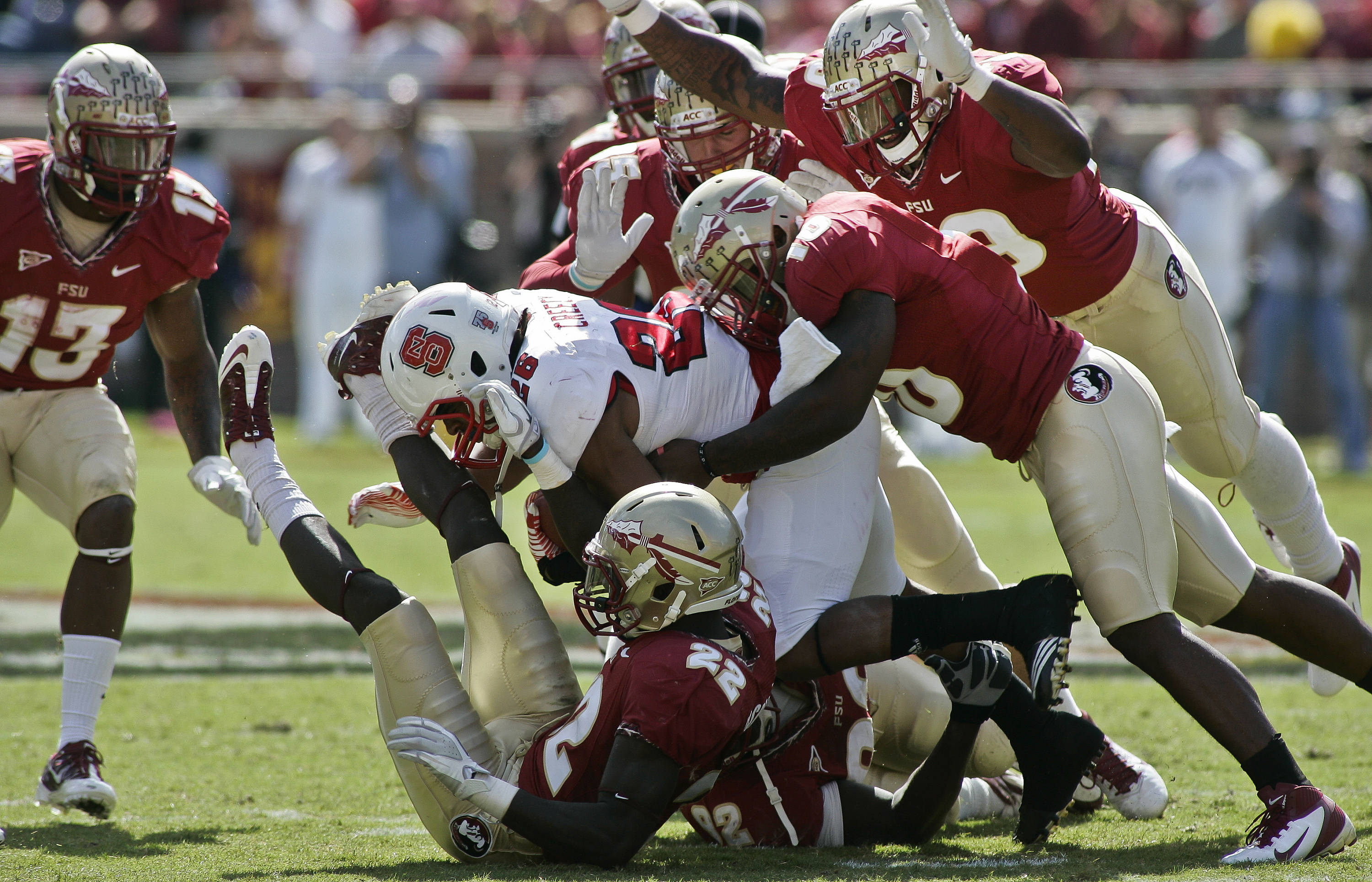 Florida State defenders swarm all over North Carolina State's Tony Creecy (26) in the second quarter of an NCAA college football game at Doak Campbell Stadium in Tallahassee, Fla., Saturday, Oct. 29, 2011. (AP Photo/Phil Sears)