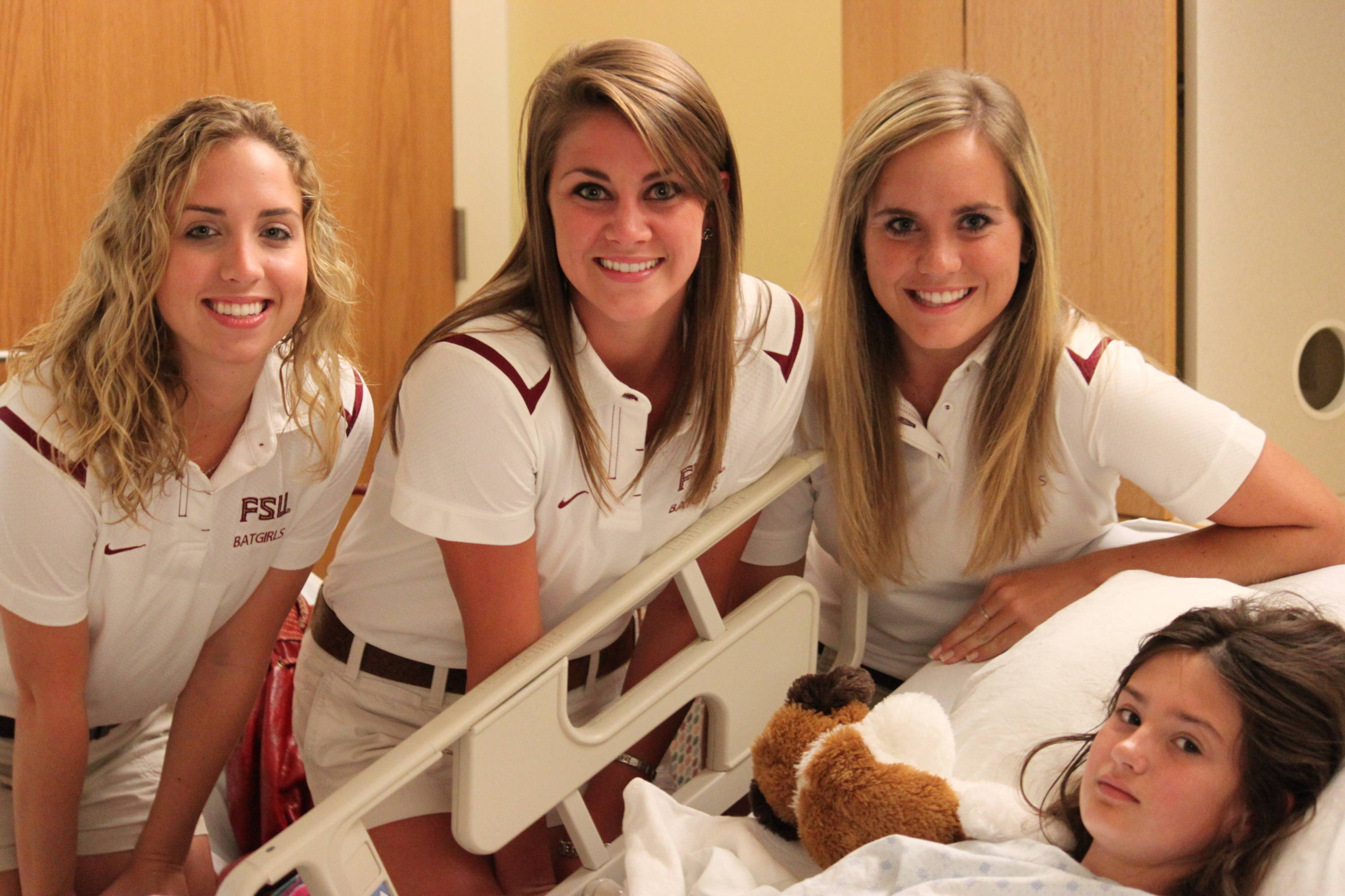 Bailey, Bret and Heidi, members of the Bat Girls, visit with children during a hospital visit on Tuesday morning.