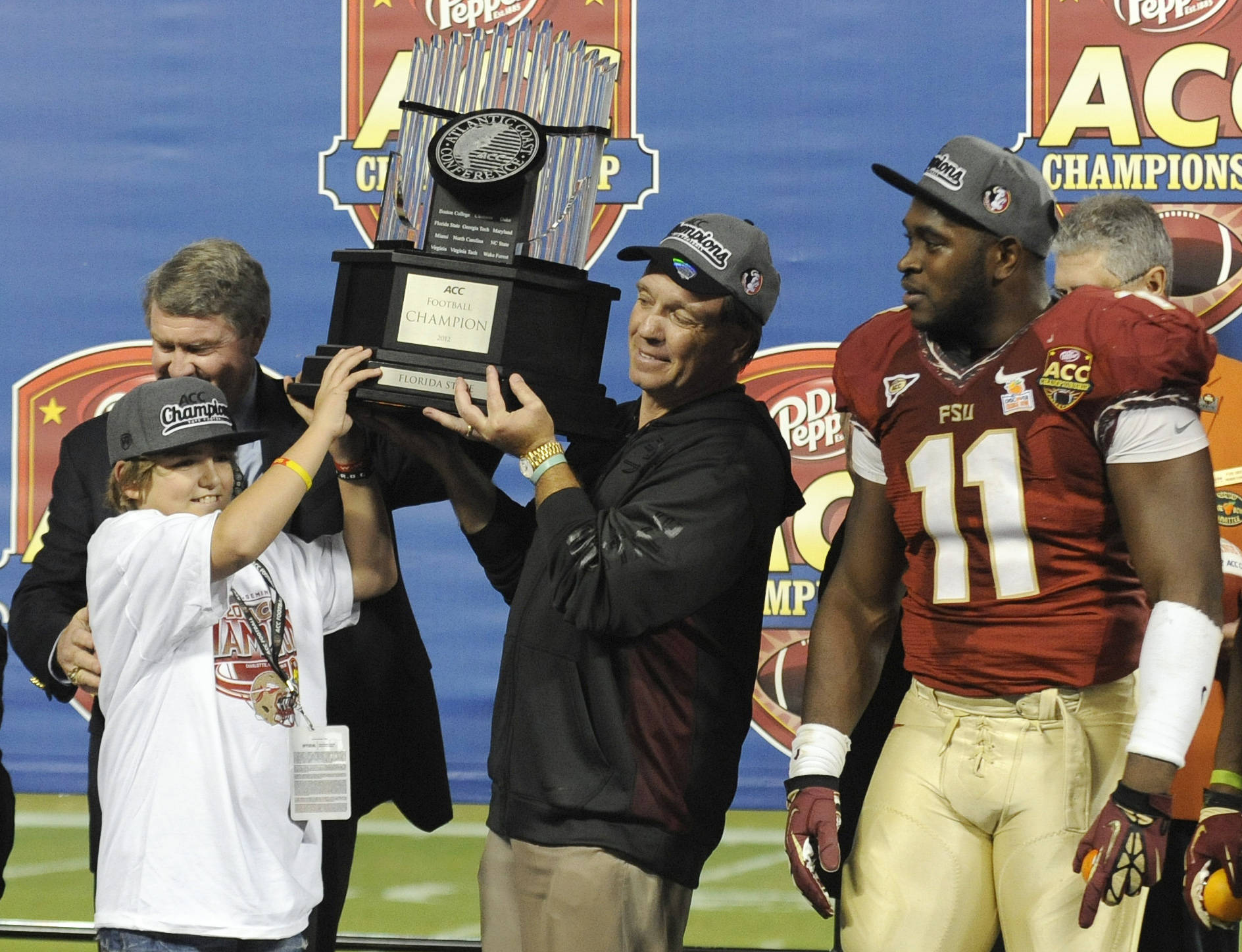 Florida State coach Jimbo Fisher, center, raises the trophy with his son, Trey, left, as Vince Williams (11) looks on after Florida State's 21-15 win over Georgia Tech in the Atlantic Coast Conference championship NCAA college football game in Charlotte, N.C., Saturday, Dec. 1, 2012. (AP Photo/Mike McCarn)