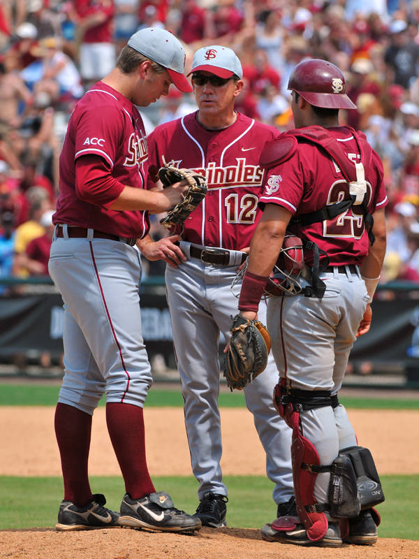 Coach Shouppe talks to pitcher Jack Posey and catcher Rafael Lopez