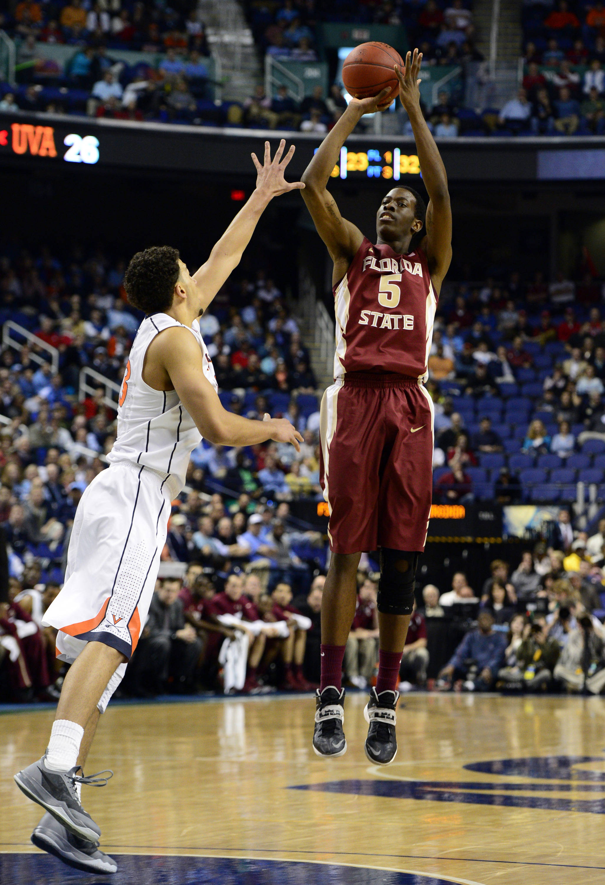 Mar 14, 2014; Greensboro, NC, USA; Florida State Seminoles forward Jarquez Smith (5) takes a jump shot over Virginia Cavaliers forward Anthony Gill (13) in the quarterfinals of the ACC college basketball tournament at Greensboro Coliseum. Mandatory Credit: John David Mercer-USA TODAY Sports
