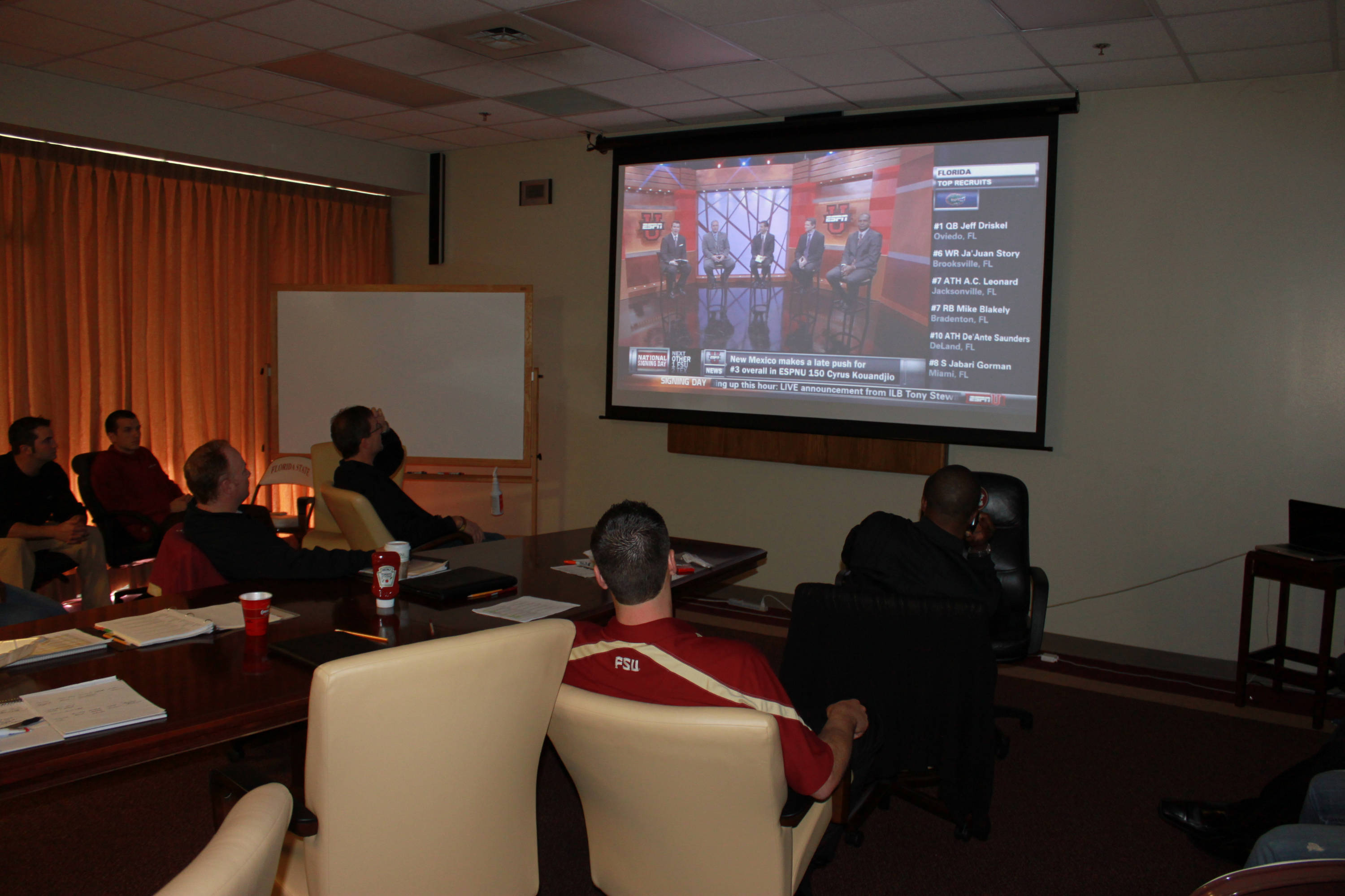 Coaches watch the live signing day coverage on ESPNU