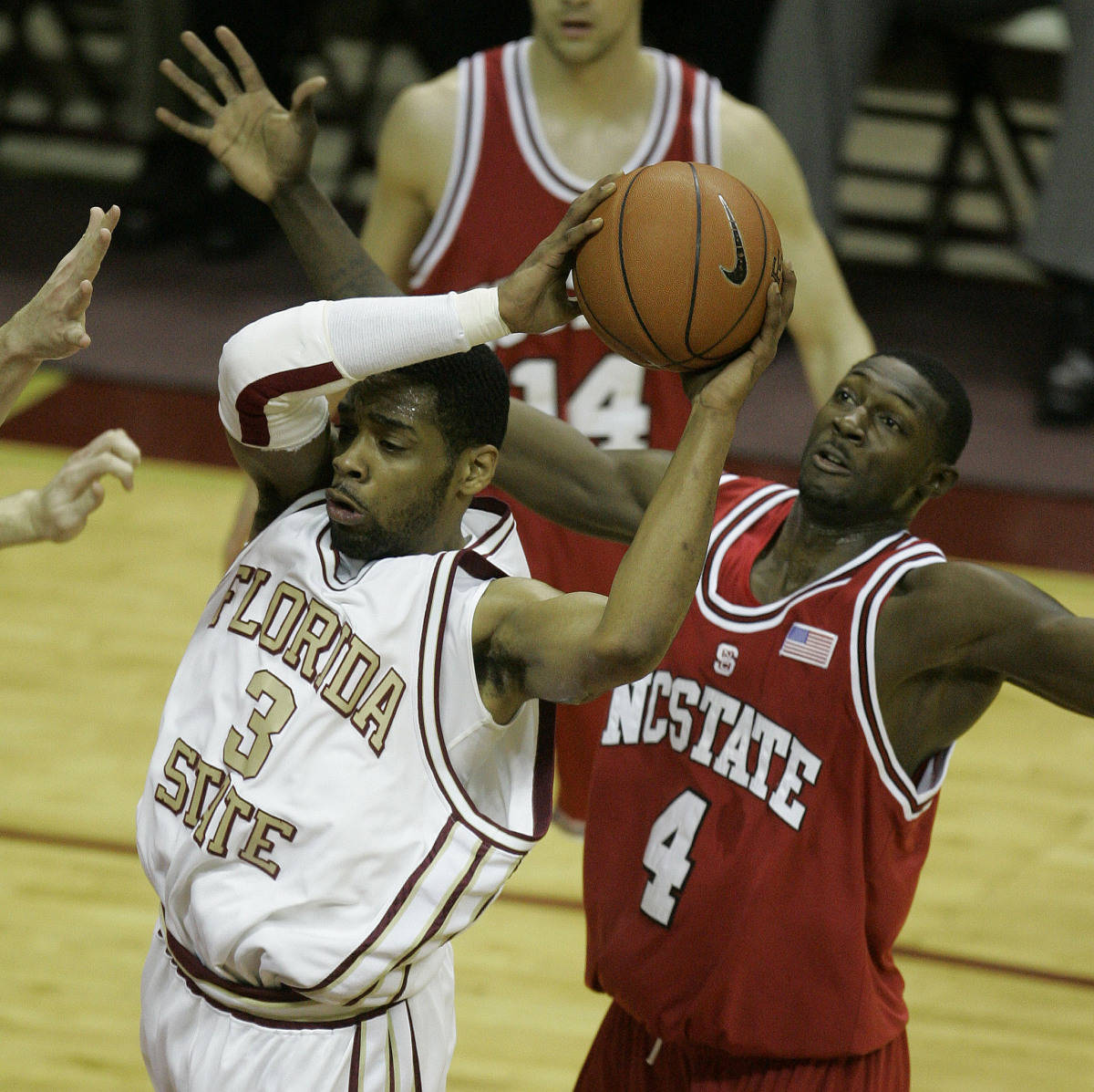 North Carolina State's Courtney Fells (4) attempts to knock the ball away from Florida State's Isaiah Swann (3) during the first half of a college basketball game, Saturday, Feb. 24, 2007, in Tallahassee, Fla.(AP Photo/Phil Coale)