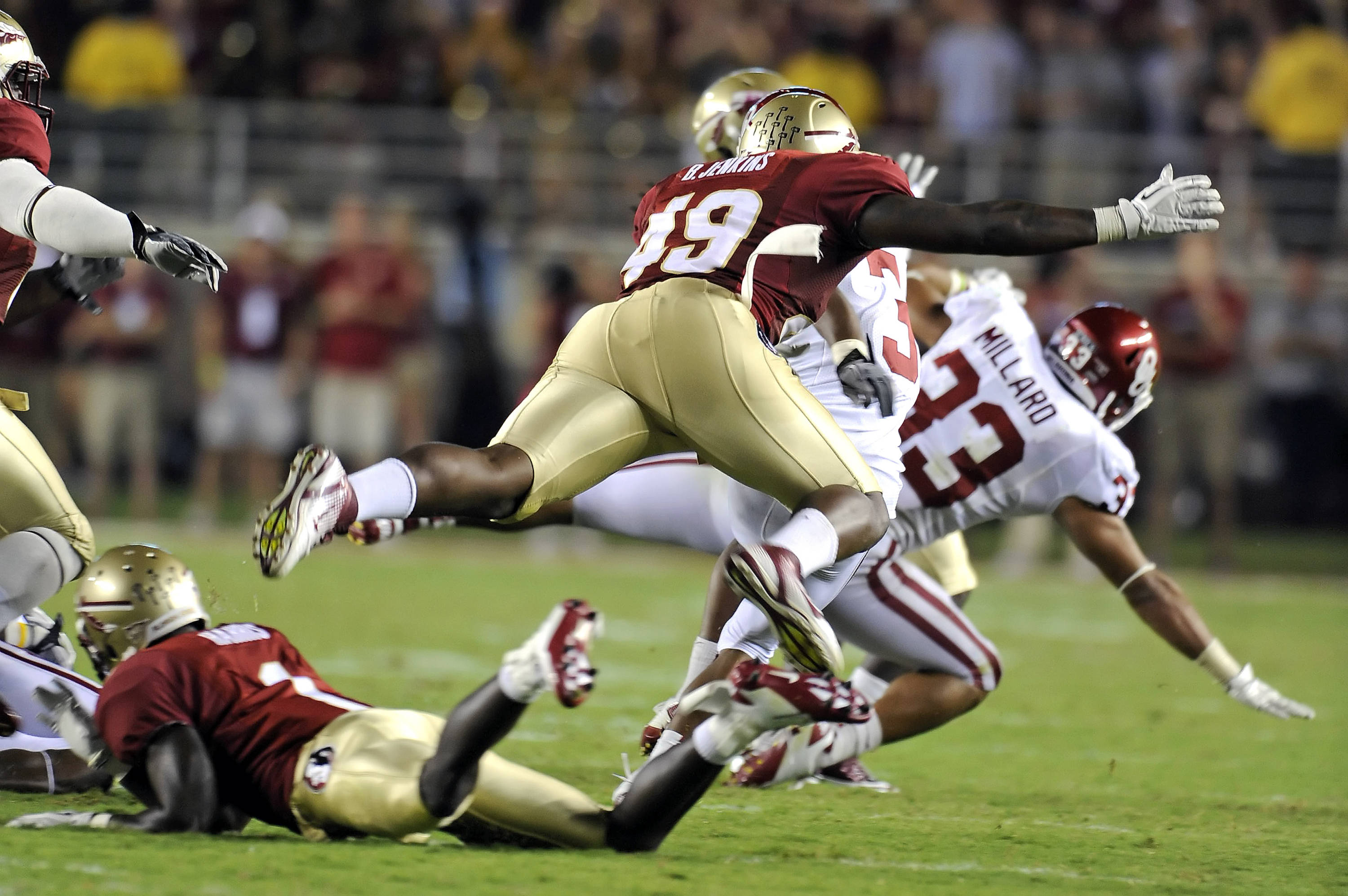 Brandon Jenkins (49) leaps to make a tackle in Florida State's matchup with No. 1 Oklahoma