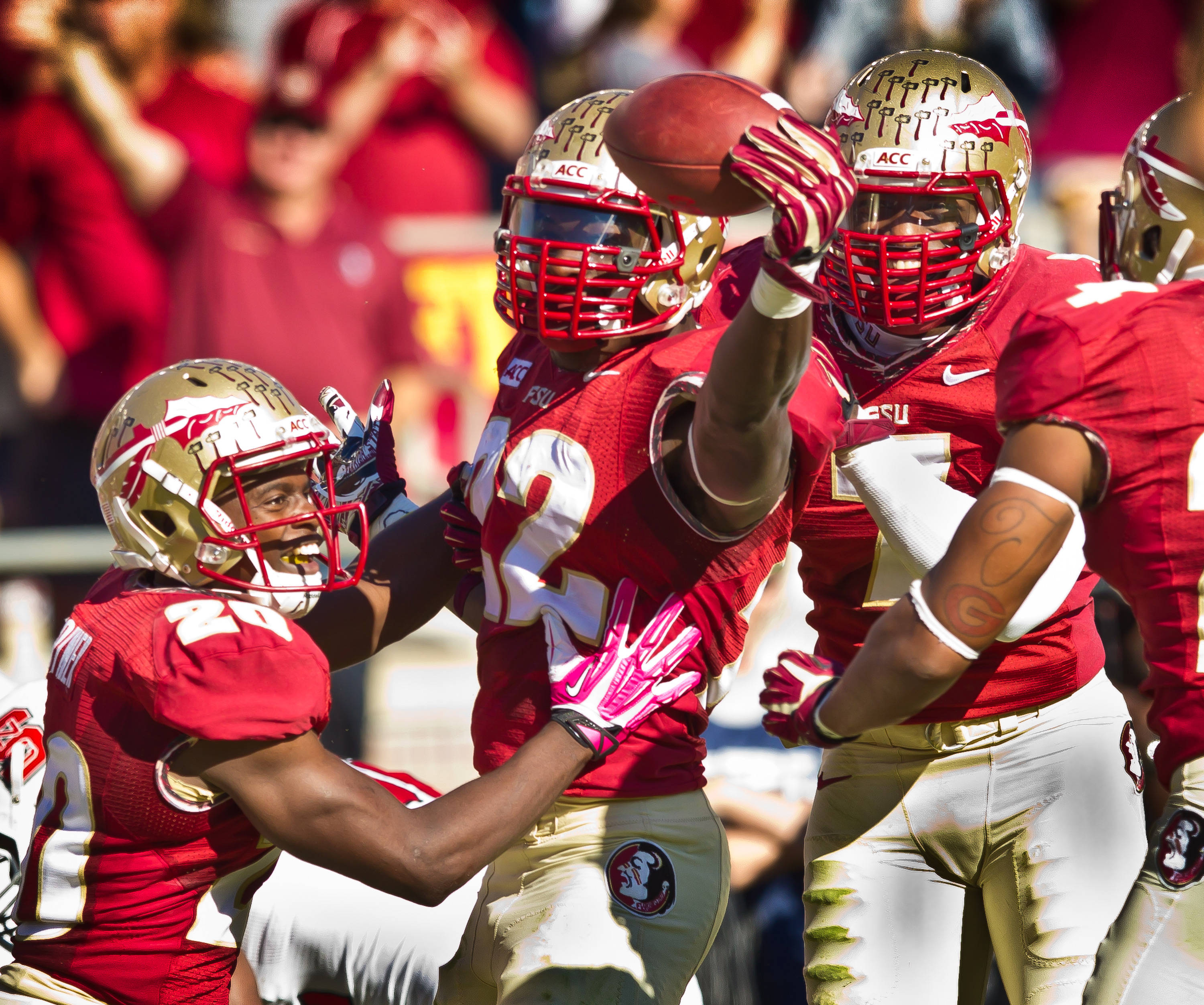 Lamarcus Joyner (20), Telvin Smith (22), and Christian Jones (7) celebrate Smith's fumble recovery against N.C. State.