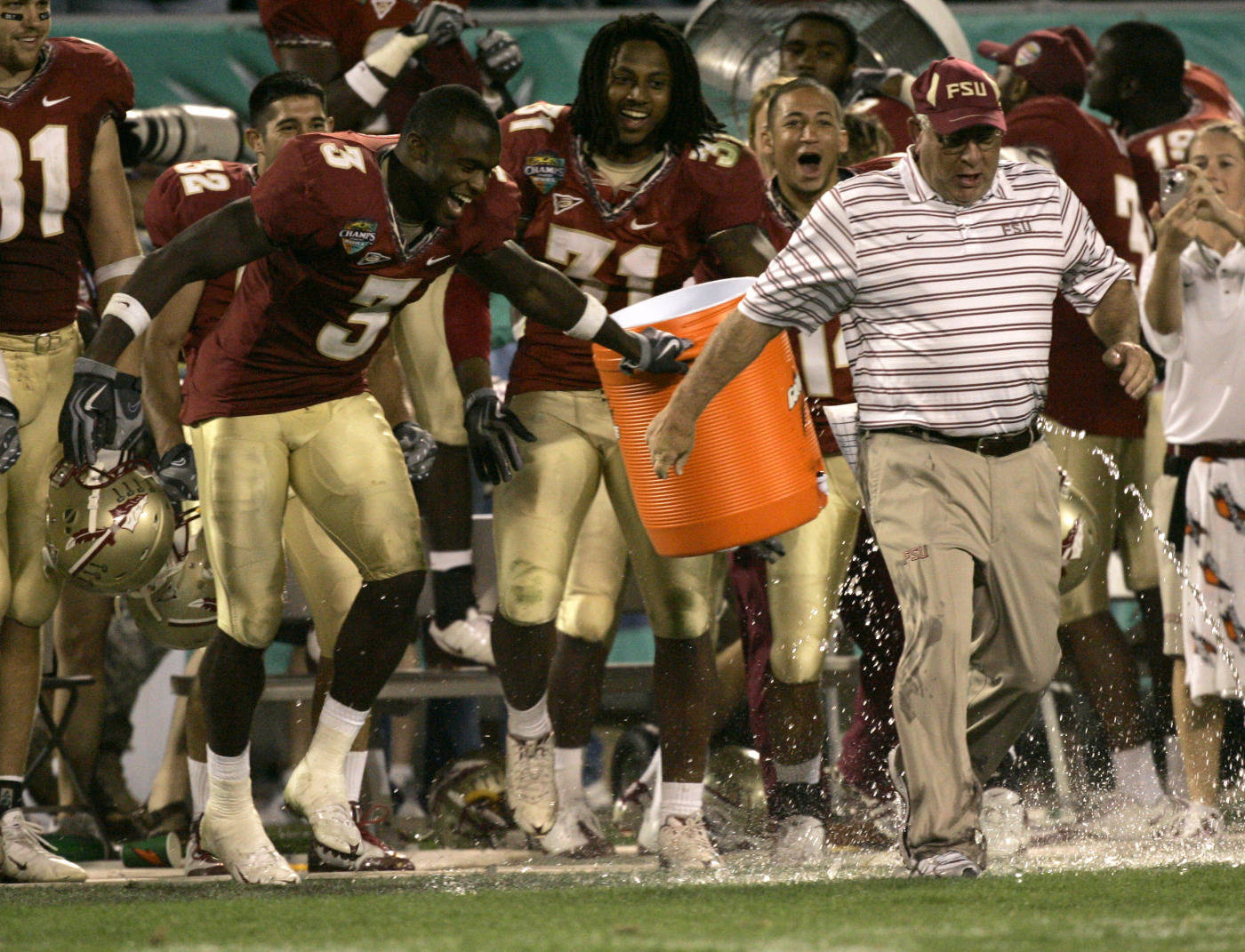 Florida State safety Myron Rolle (3), linebacker Toddrick Verdell (31) and teammates celebrate after dousing defensive coordinator Mickey Andrews, right, during the final moments of the Champs Sports Bowl. (AP Photo/John Raoux)