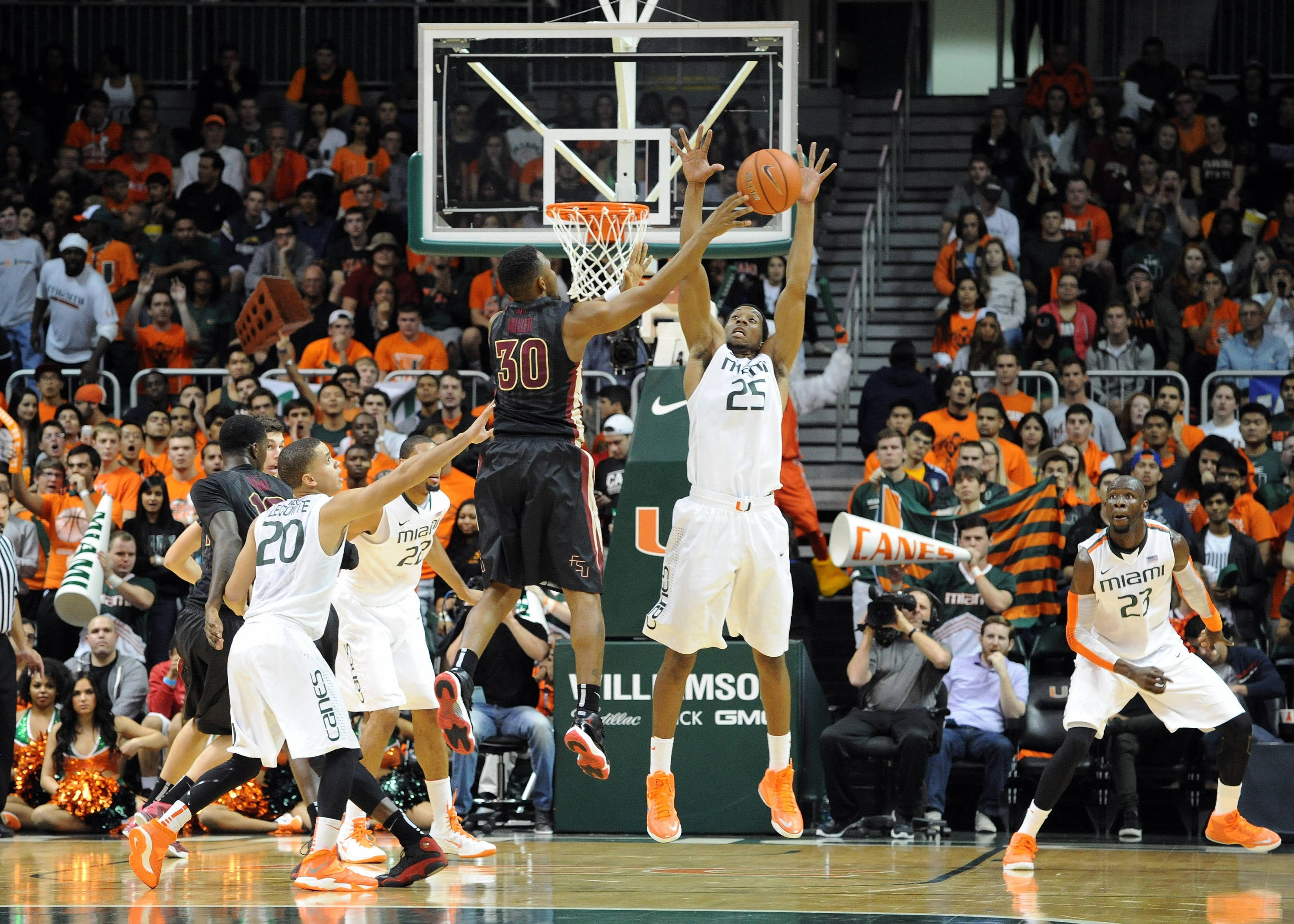 Jan 15, 2014; Coral Gables, FL, USA; Seminoles guard Ian Miller (30) is pressured by Miami Hurricanes guard Garrius Adams (25) during the second half. Steve Mitchell-USA TODAY Sports