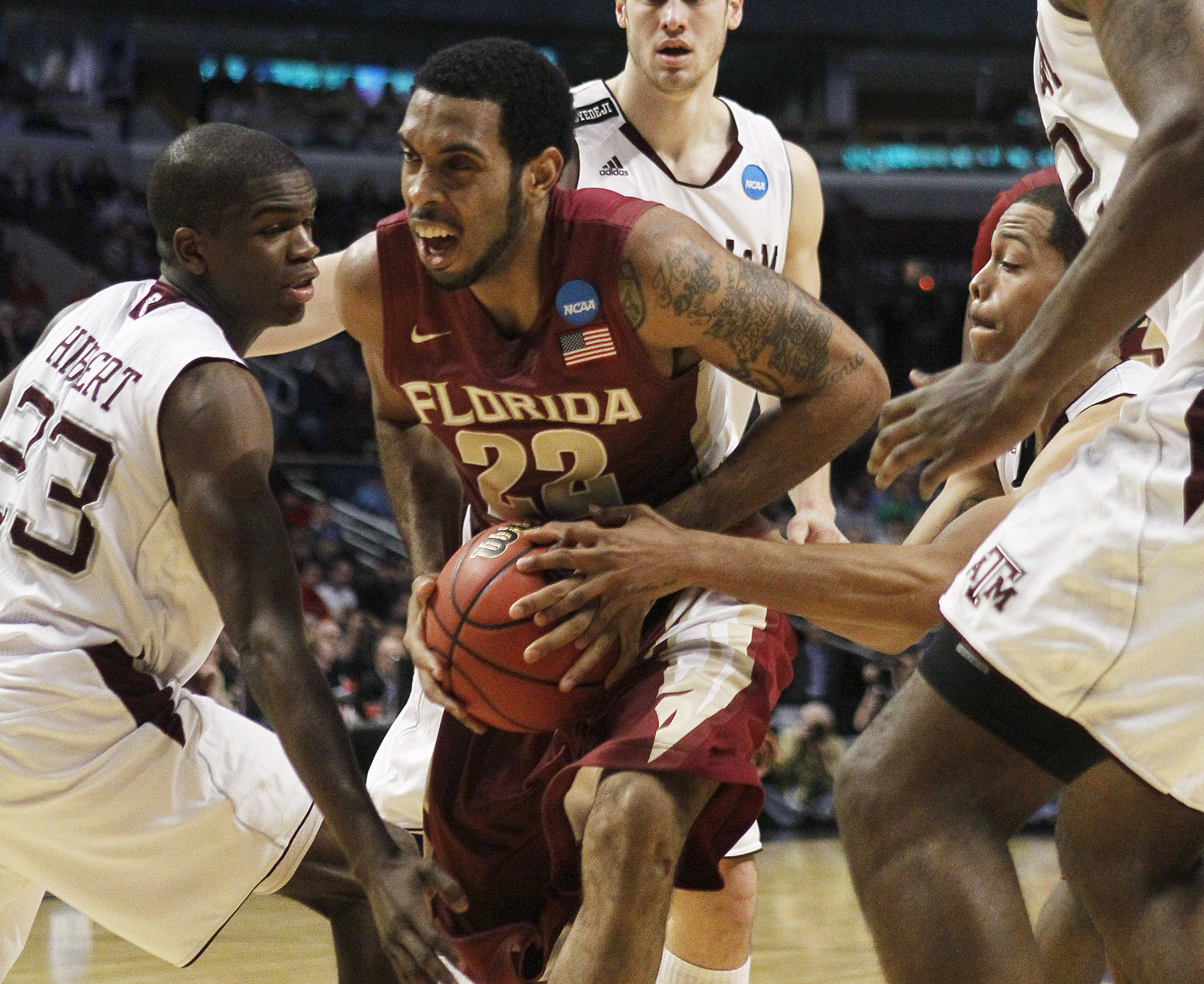 Texas A&M's Naji Hibbert and B.J. Holmes defend Florida State's Derwin Kitchen as he drives the lane in the first half. (AP Photo/Charles Rex Arbogast)