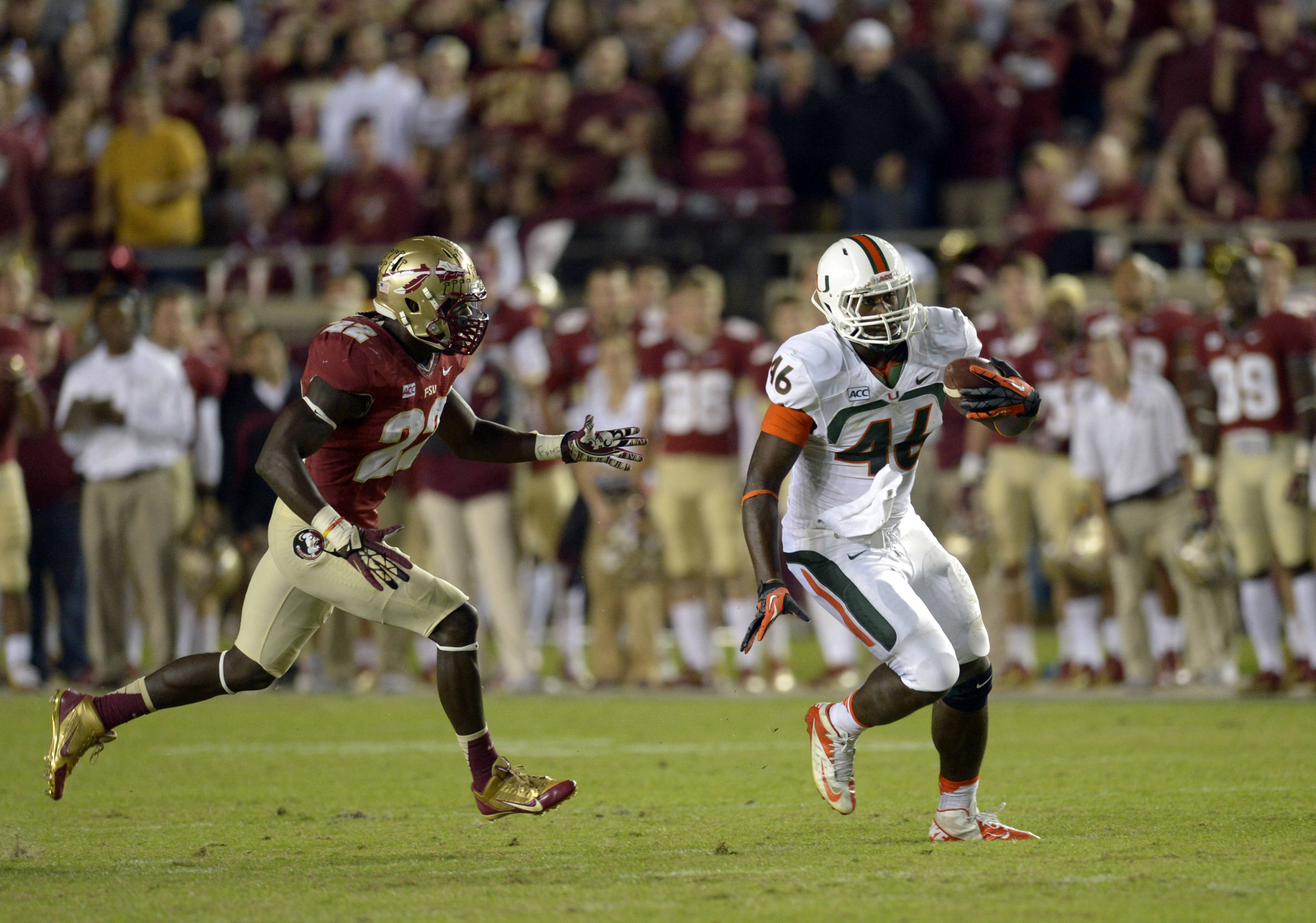 Miami Hurricanes tight end Clive Walford (46) carries up the field past Florida State Seminoles linebacker Telvin Smith (22) during the first quarter at Doak Campbell Stadium. Mandatory Credit: John David Mercer-USA TODAY Sports