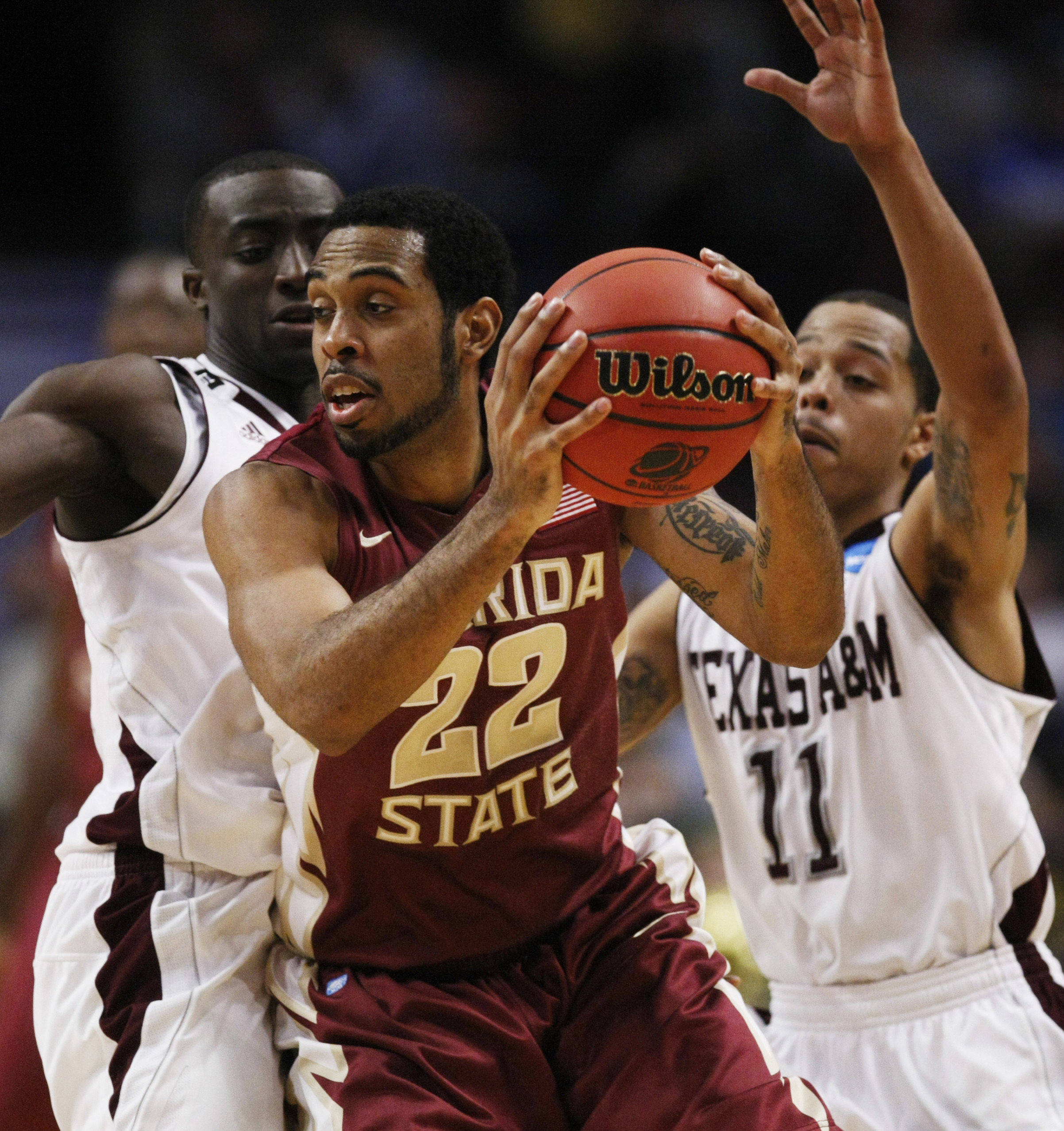 Florida State's Derwin Kitchen is defended by Texas A&M's Andrew Darko, left, and B.J. Holmes in the second half of a second-round NCAA Southwest Regional tournament college basketball game in Chicago, Friday, March 18, 2011. Kitchen was high scorer for Florida State with 15 points in their 57-50 win. (AP Photo/Charles Rex Arbogast)