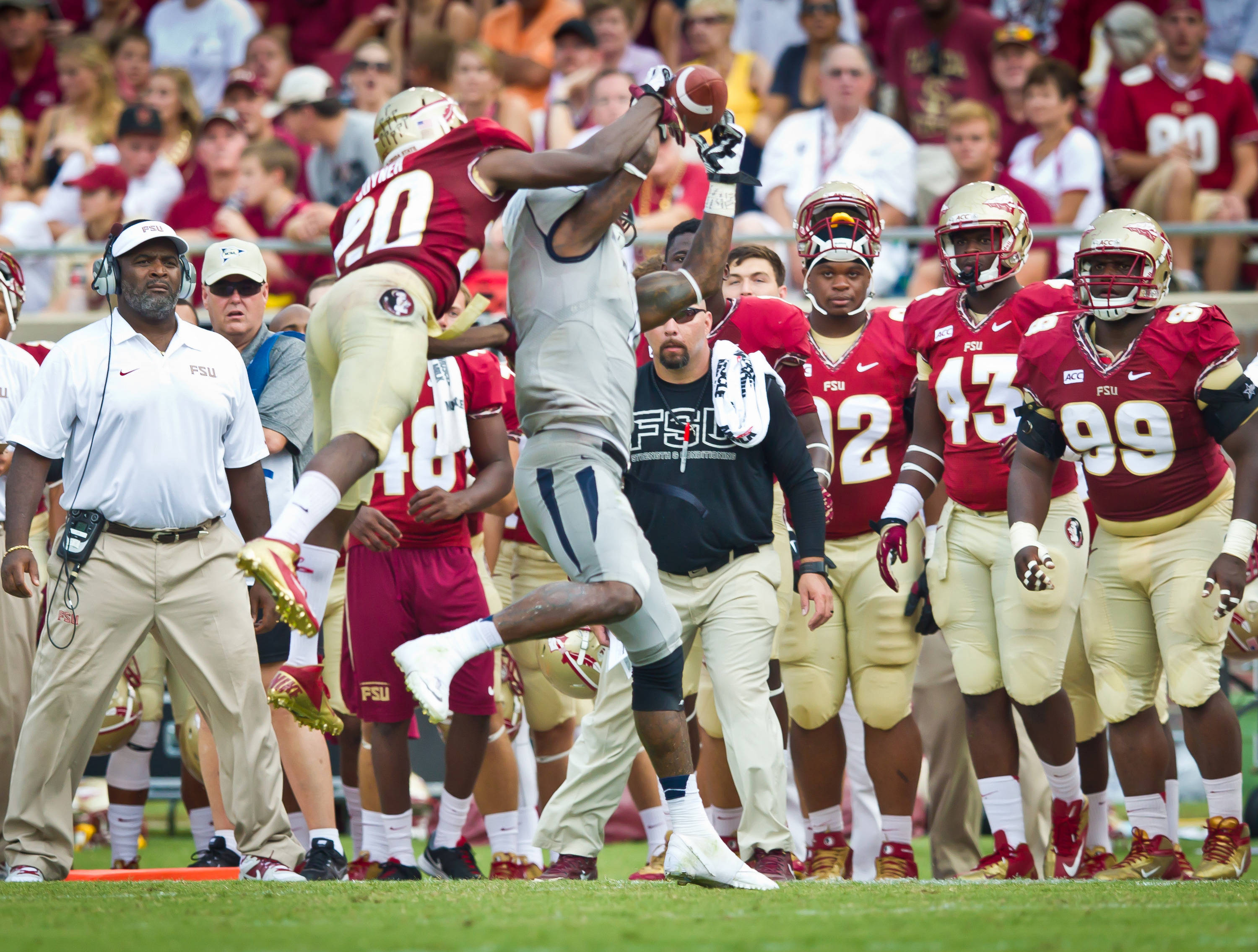Lamarcus Joyner (20) breaks up a pass in front of the FSU bench.