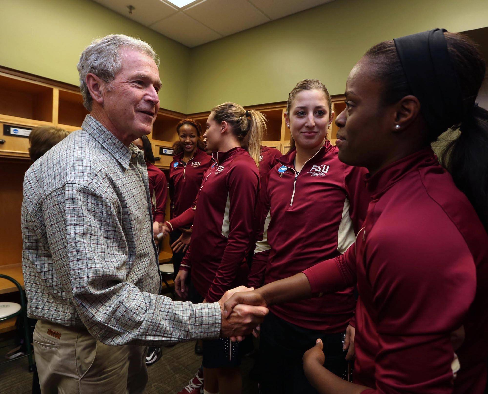 Former President George W. Bush shakes hands with Florida State Morgan Tolels, right, and Leonor Rodriquez, center, before their second-round NCAA college women's basketball game against Baylor, Tuesday, March,  26, 2013, in Waco, Texas. (AP Photo/Florida State University, Rod Aydelotte, Pool)
