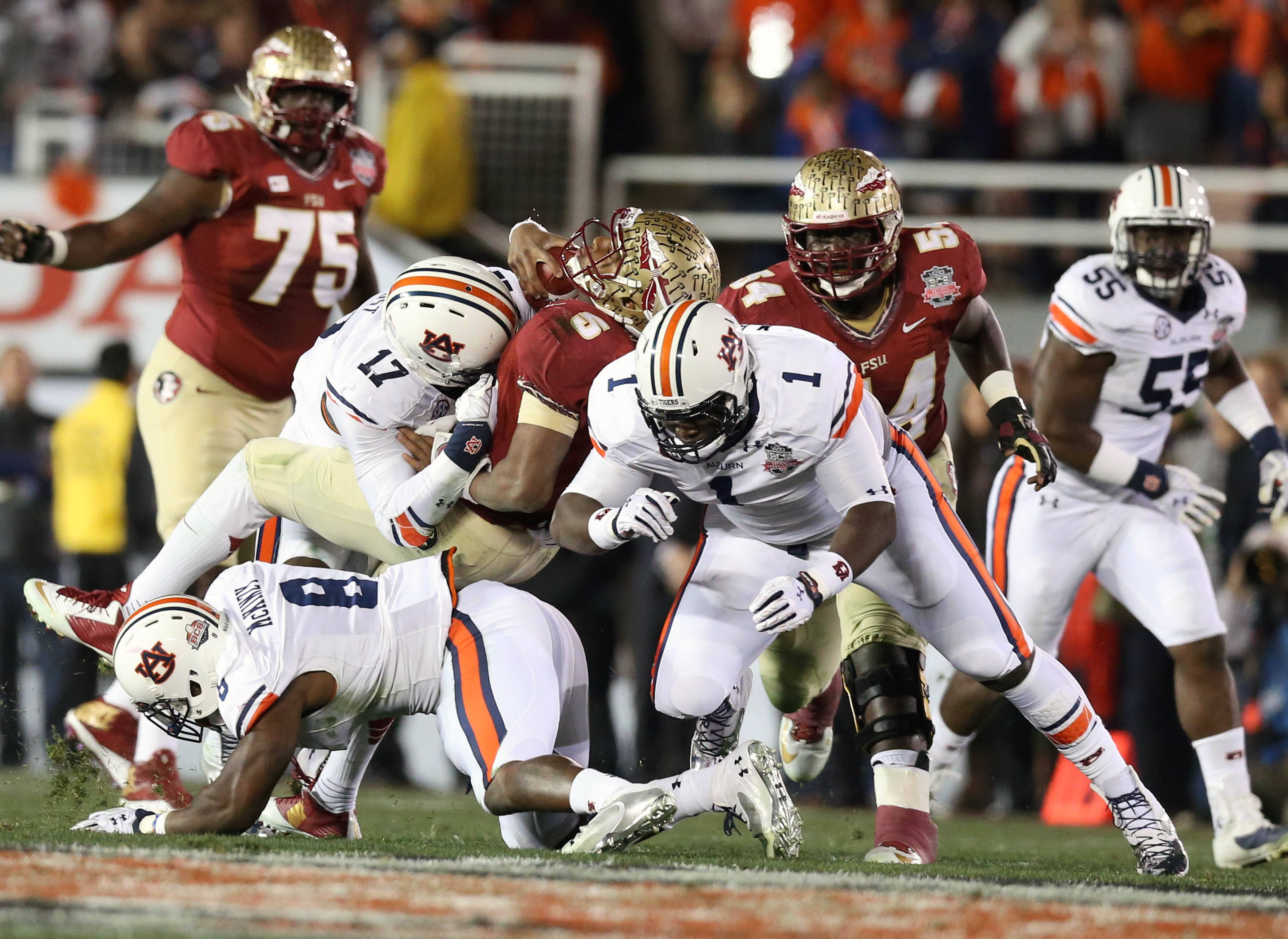 Jan 6, 2014; Pasadena, CA, USA; Florida State Seminoles quarterback Jameis Winston (5) is tackled by Auburn Tigers linebacker Kris Frost (17), Cassanova McKinzy (8) and Montravius Adams (1) during the first half of the 2014 BCS National Championship game at the Rose Bowl.  Mandatory Credit: Matthew Emmons-USA TODAY Sports